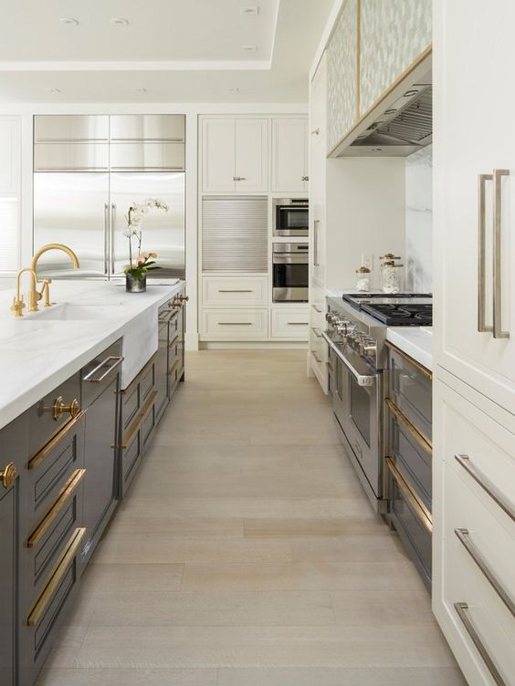 A beautiful blend of brass & stainless… The white cabinets and marble countertop tie together the brass hardware and cabinet pulls with the stainless appliances and lower grey cabinetry.   (Courtesy of Pinterest)