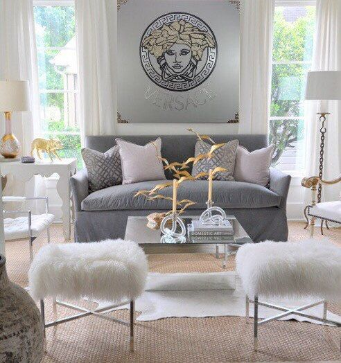 The gold piece (birds?) in the center of the coffee table acts as a focal point, but it's complemented by the gold lamps and accents on the perimeter. The presence of gold and silver in the artwork ties it all together.  (   Courtesy of Pinterest   )