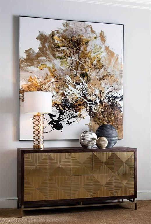 The cooler grey, black and silver found in the art piece is tied together with the surrounding gold furnishings by virtue of the decorative vases placed on top of the credenza.   (Courtesy of Pinterest)