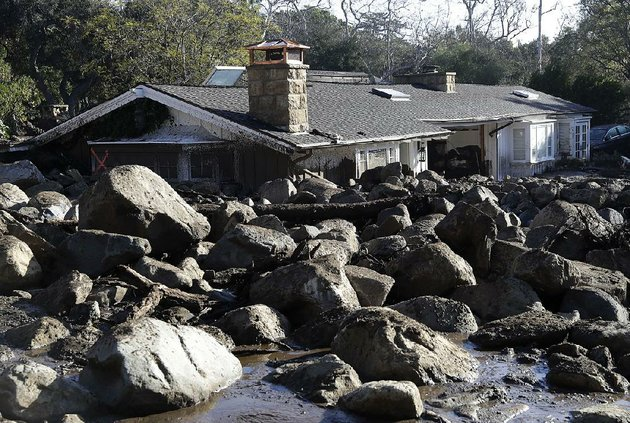 Public Works is grappling with the boulders that came down with the Mudslide.   Photo by Mike Eliason.