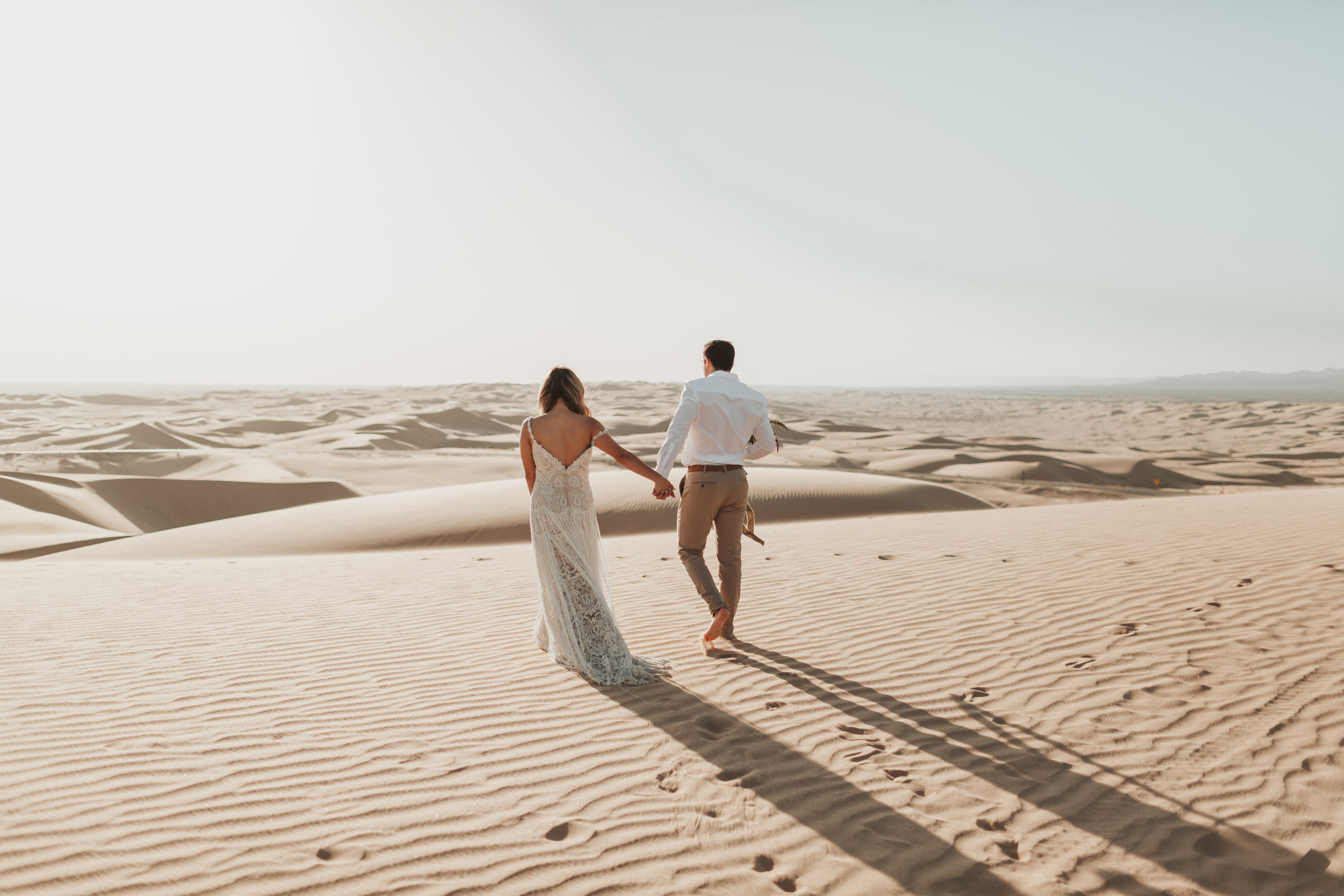 couple walking in sand dunes together holding hands