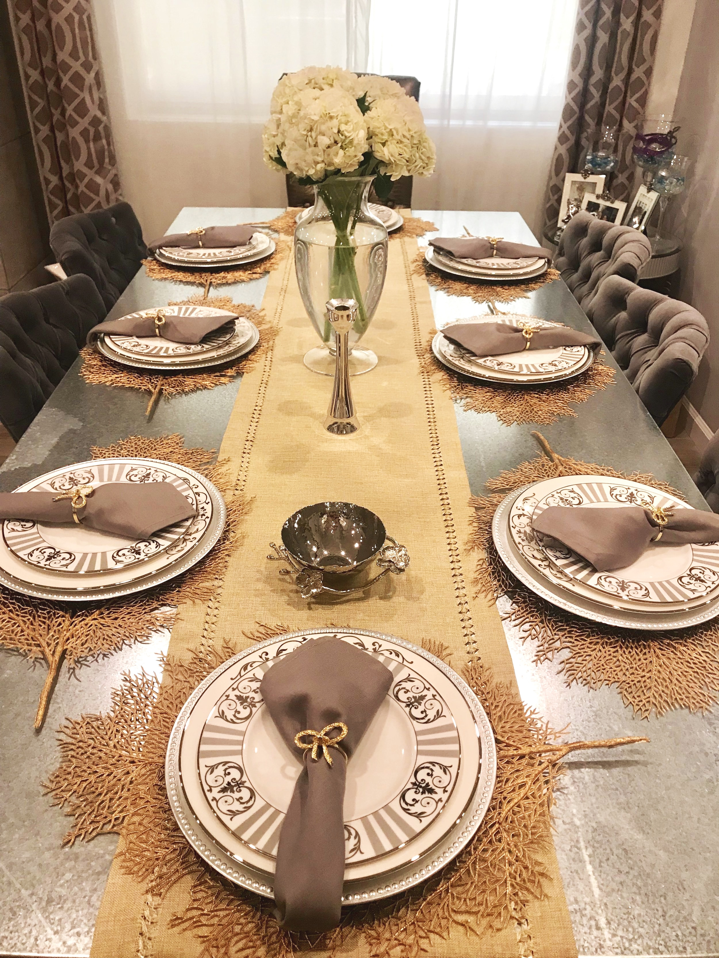 Take a look here, we've incorporated grey napkins with gold ribbon rings, silver and white plates on a silver charger followed by gold leaf placemats.