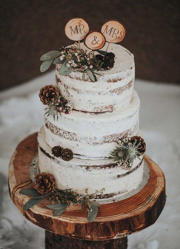 Naked wedding cake _ Rustic wedding cake decorated with pine cones + slice of wood as wedding cake topper display on slice of wood_.jpeg