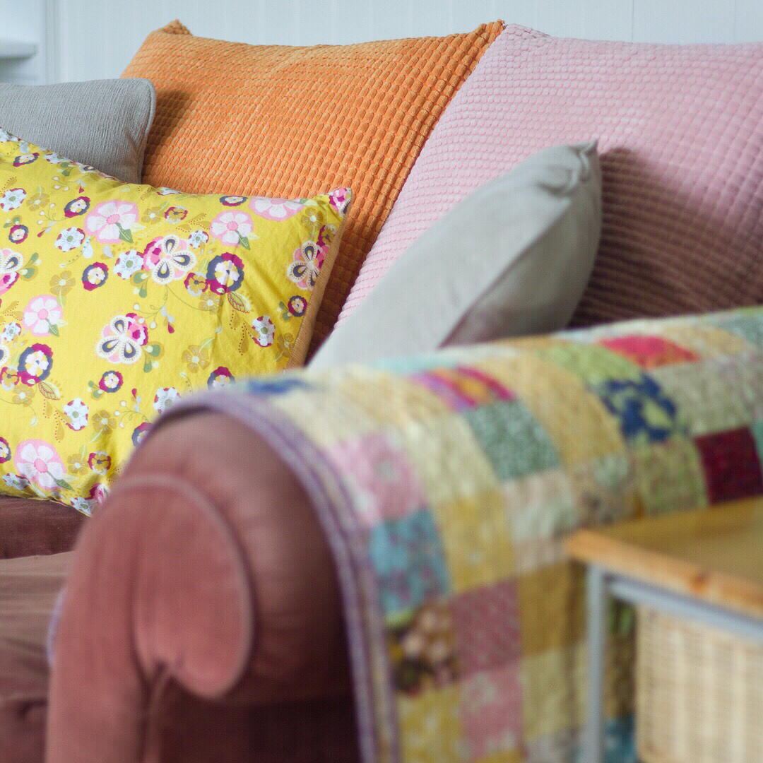 Yellow, Pink and Orange Pillows on Couch - via www.cottagemagpie.com