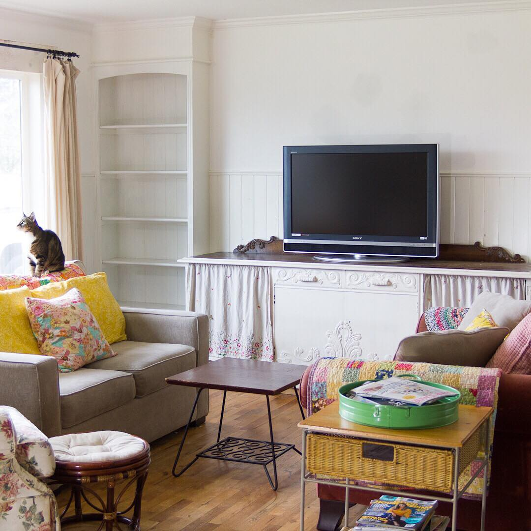 Cheery Pillows and Kitty in Living Room - via www.cottagemagpie.com