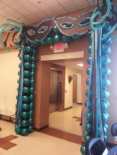 Clever placement of balloons here has transformed this entrance into gigantic matching masks with a pearl drape