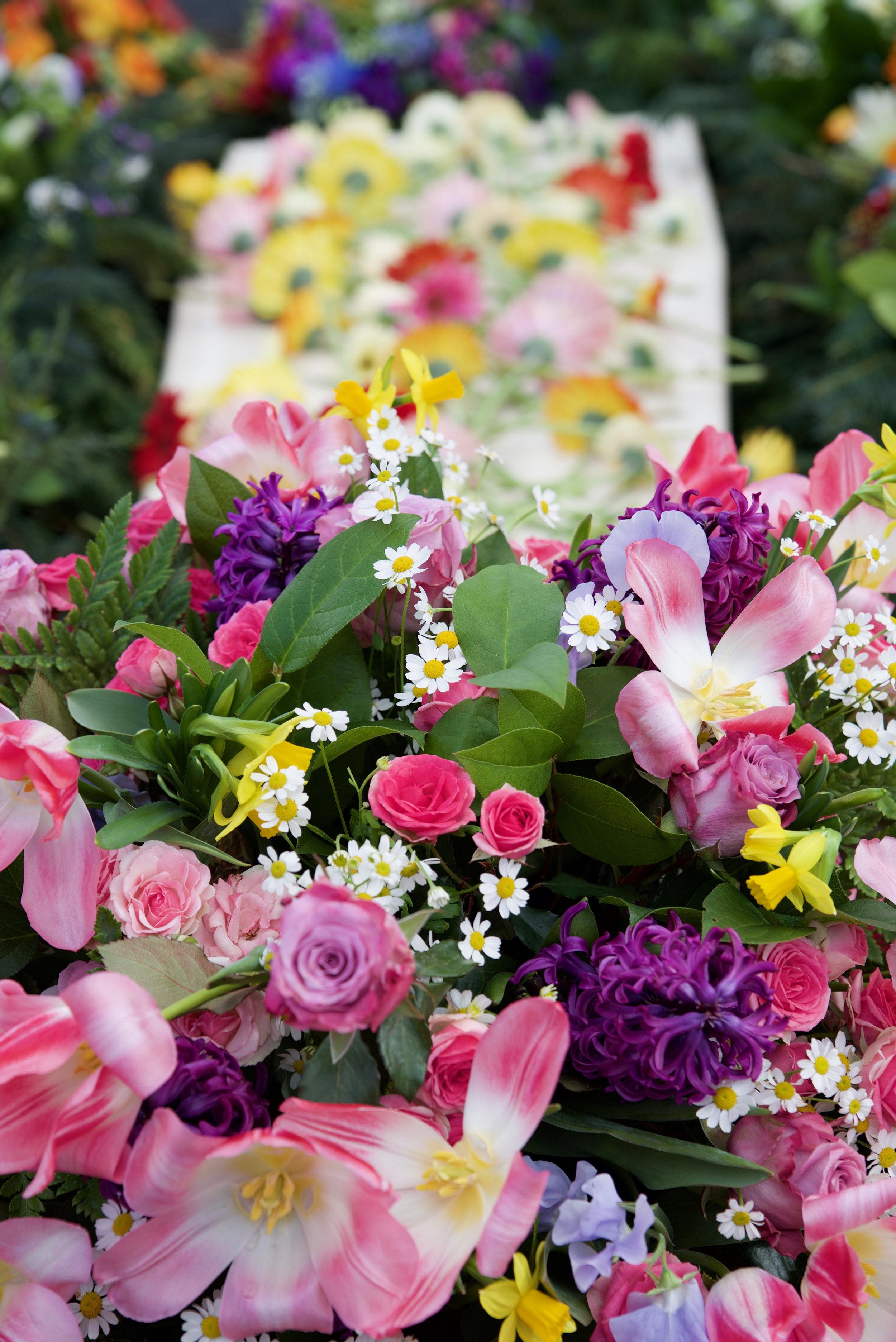 Bloemen op kist in graf - Afscheidsfotografie x STiP Fotografie