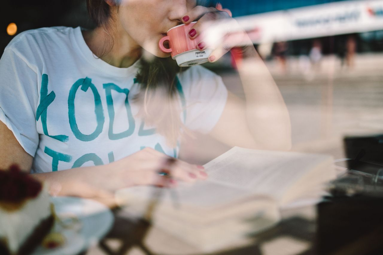 kaboompics_Young woman reading a book and holding cup of coffee.jpg