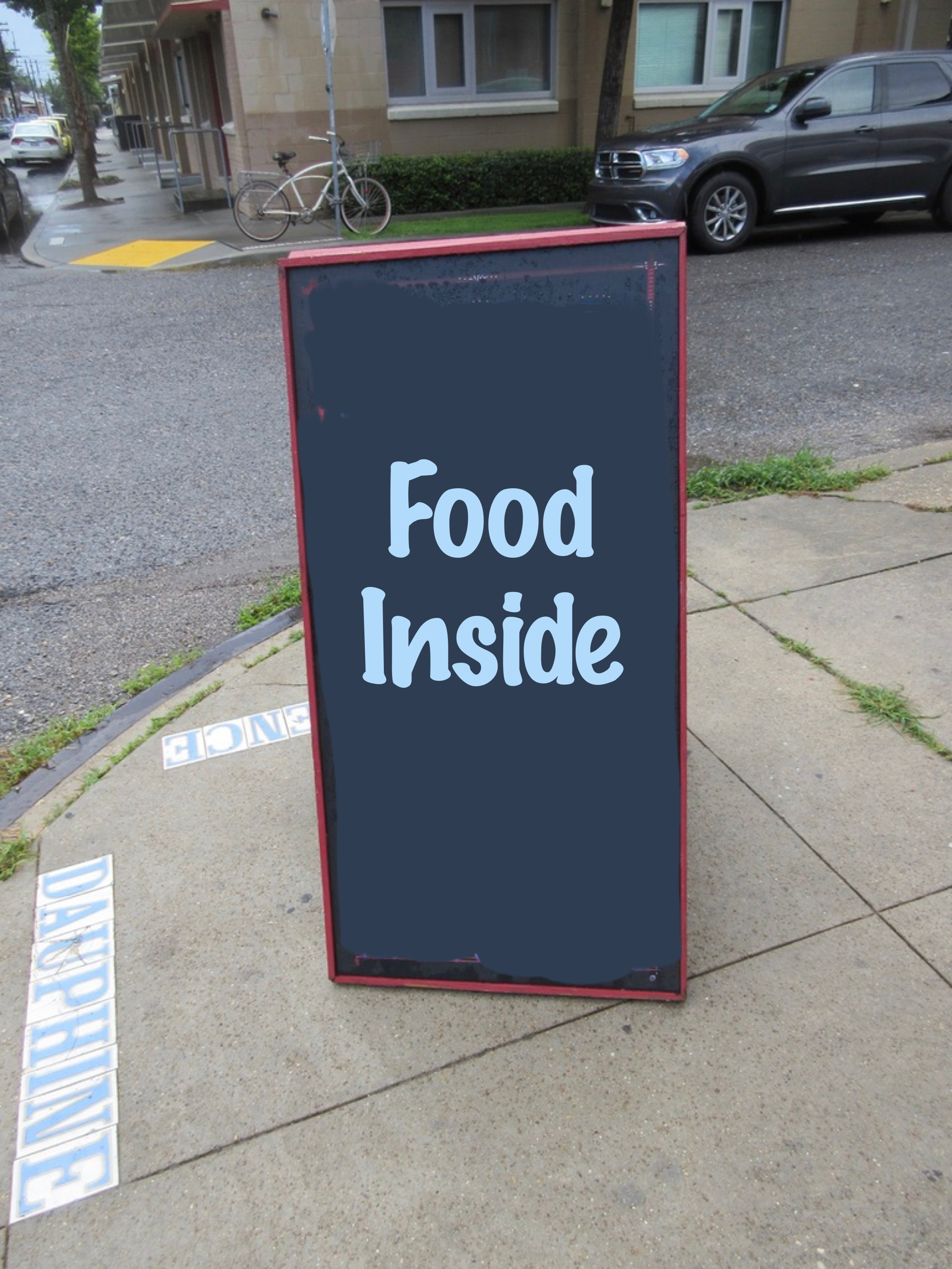 "Sandwich board that says ""Food inside""."