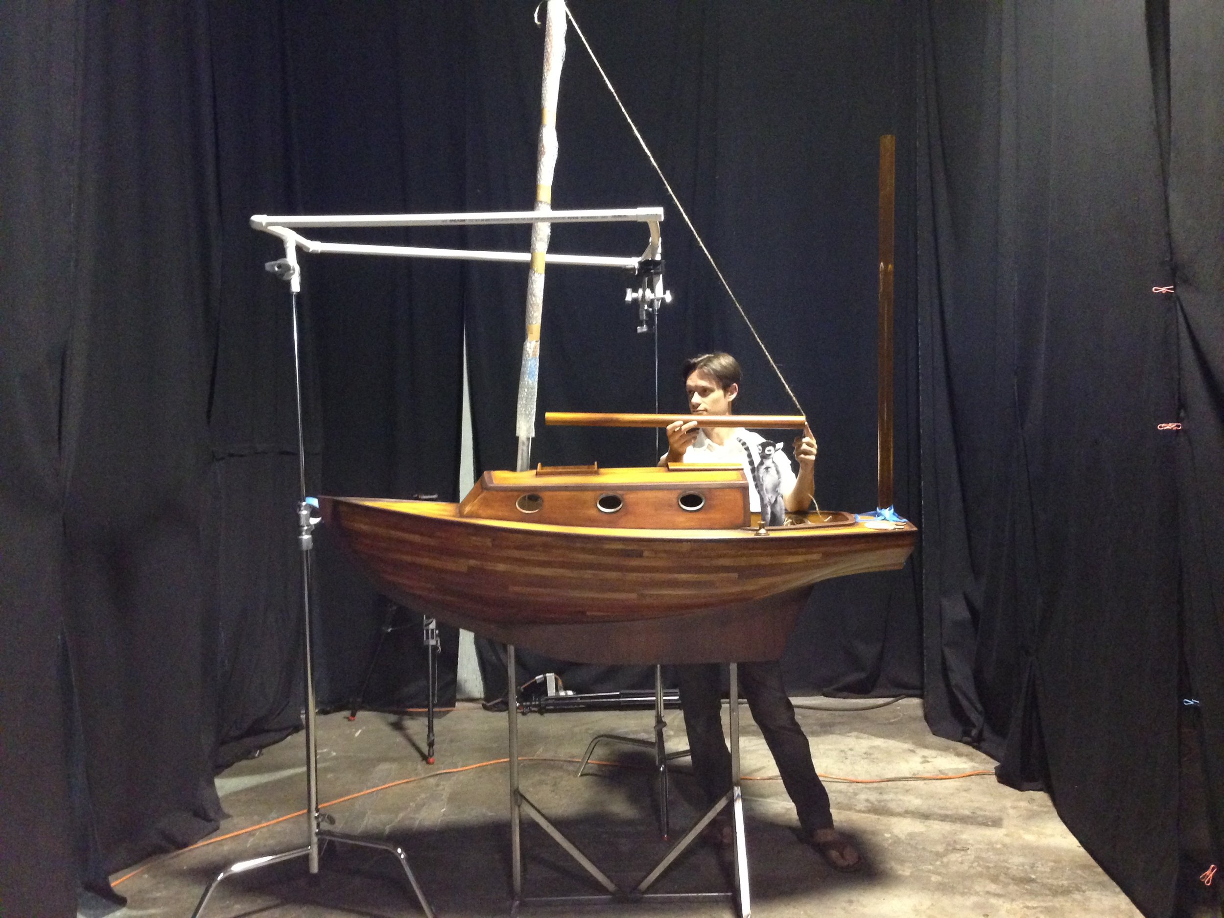 Director of Photography Reijean Heringlake inspecting Bernard's boat with a paper cutout stand-in for Bernard.