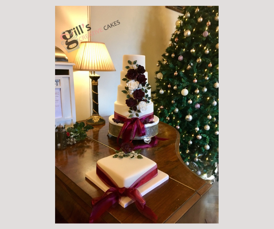 Ruby and White Winter wedding cakes displayed on piano.png