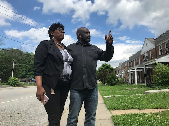 Pastor Michael and Miss Connie talk in front of her home, which had six feet of water in her basement, and now is filled with a mess of water logged debris.