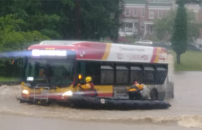 Rescuers pull people trapped on bus amid the six foot deep torrent.