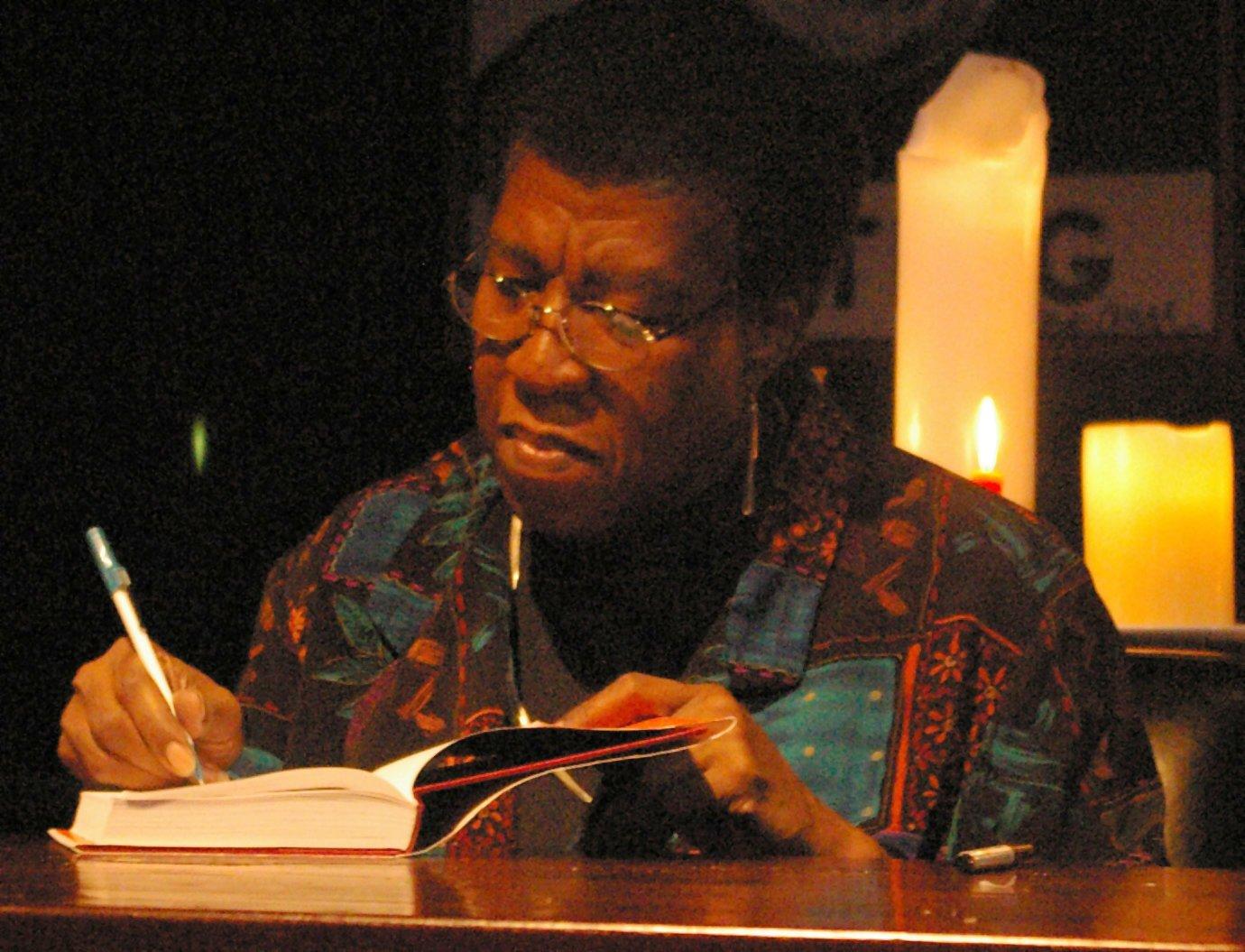Octavia E. Butler signing a copy of her book  Fledgling.  Photo credit: Nikolas Coukouma