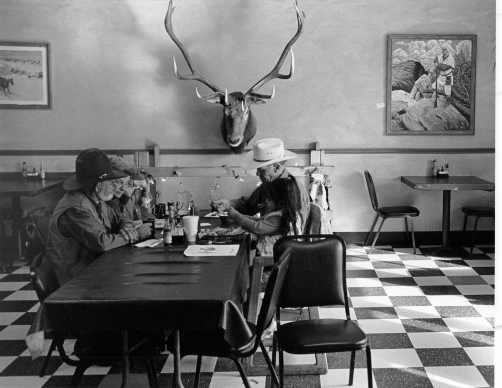 Family table, Aztec Restaurant, Aztec, New Mexico.  Walking across the restaurant to look at a painting, I saw this family talking at the dinner table like we all did back in the day before cell phones.