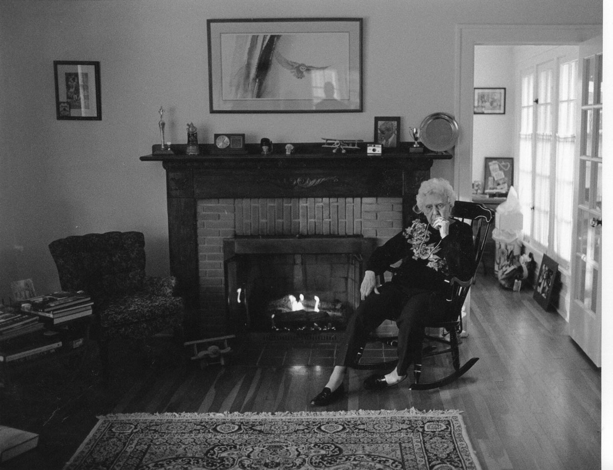 Working in the available light without flash let me capture my Aunt Margaret lost in thought at my open house.  The Kodak Instamatic camera she and her sisters gave me is on the fireplace mantle, along with a hand-crafted model of a Stearman biplane my father made for me. Thank you, Aunt Margaret, Aunt Julia, and Aunt Evelyn. Thank you, Dad. God rest all of you.