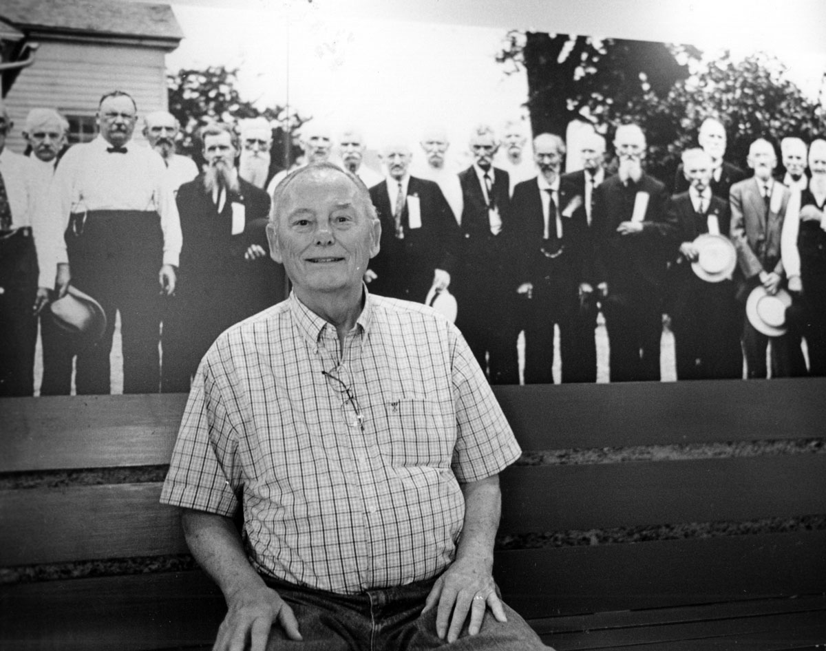 Inside the museum, Lou Wagner poses next to the image of his grandfather, Sgt. Timothy Metzler, in a mural print of a photo of a reunion of 103rd O.V.I. veterans.