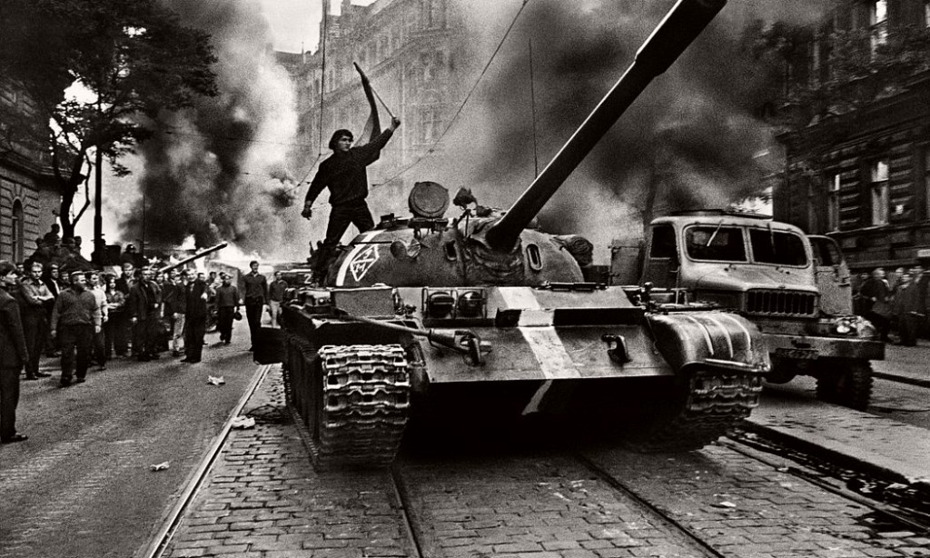 A Soviet Soldier stands on a tank, invading Prague.