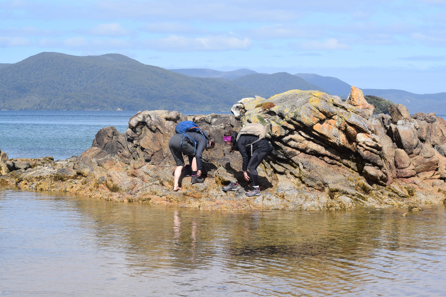 Kat and Becca remove their boots to get off our little island. It was a peninsula when we got there...