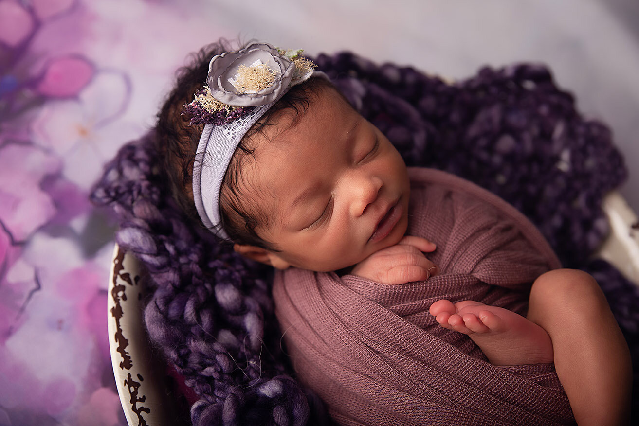 newborn baby girl purple flowers in bowl close up.jpg