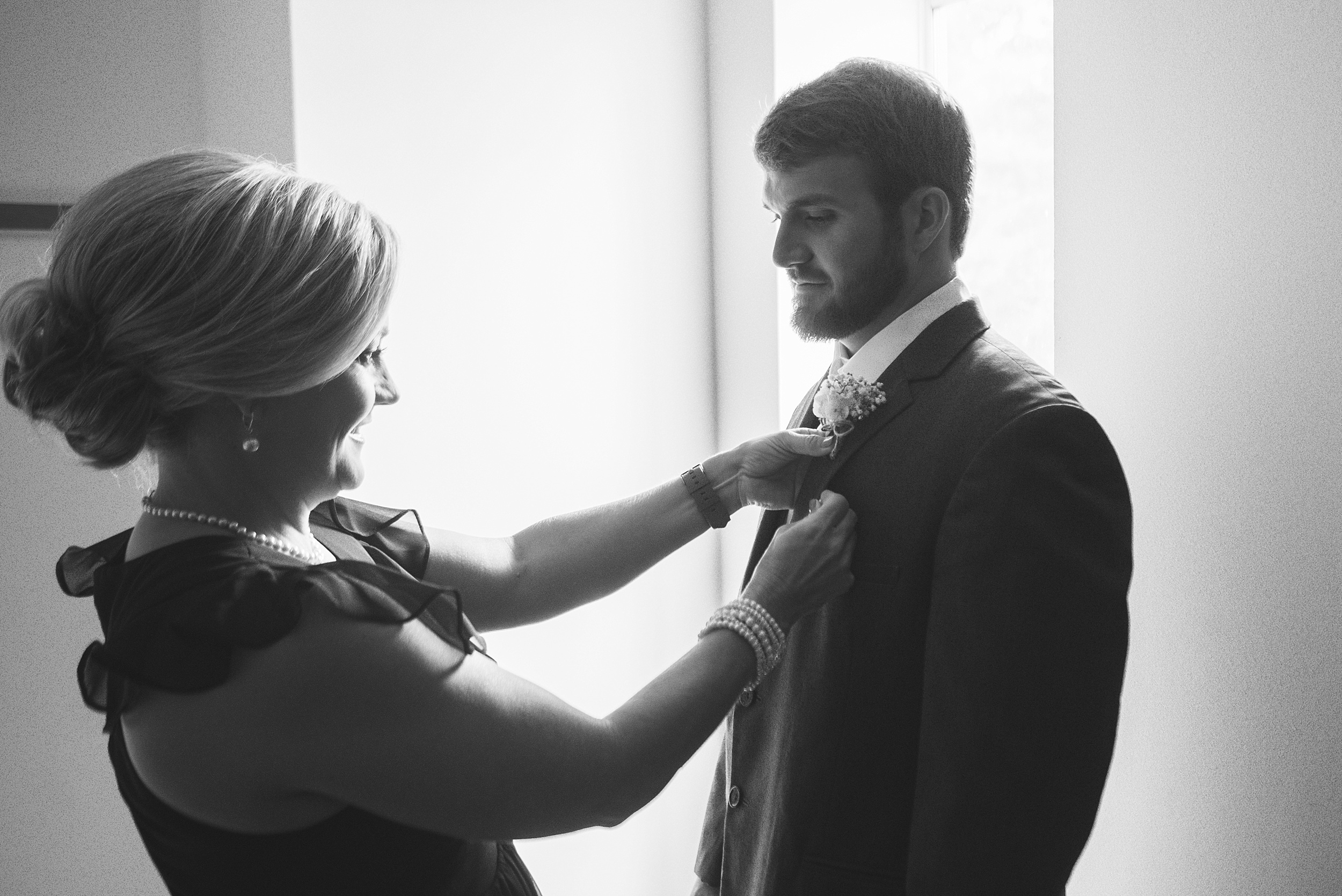 Mother of groom pins on the groom's boutonniere in front of a window