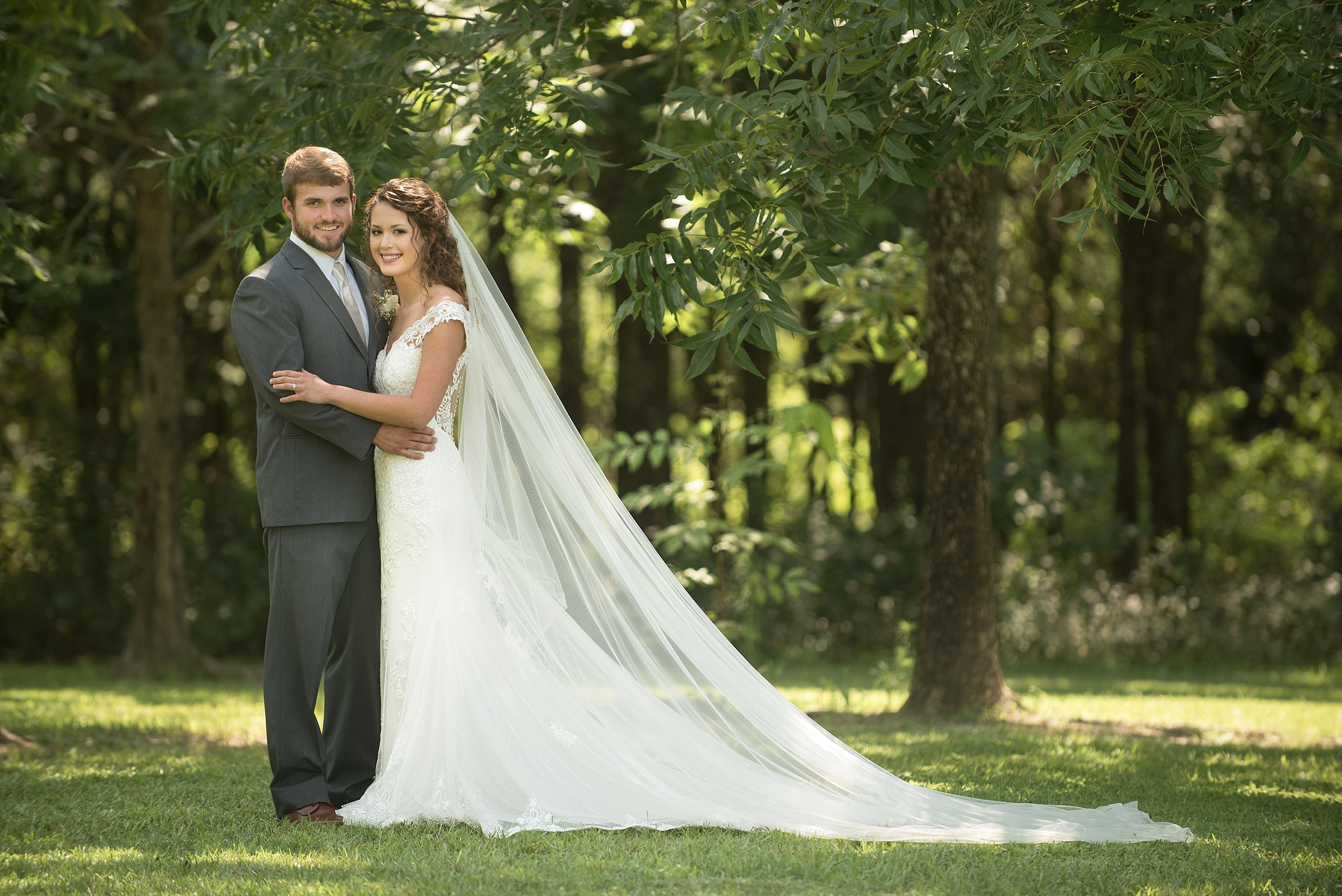 groom in gray tuxedo embraces bride in lace wedding dress with cathedral length veil