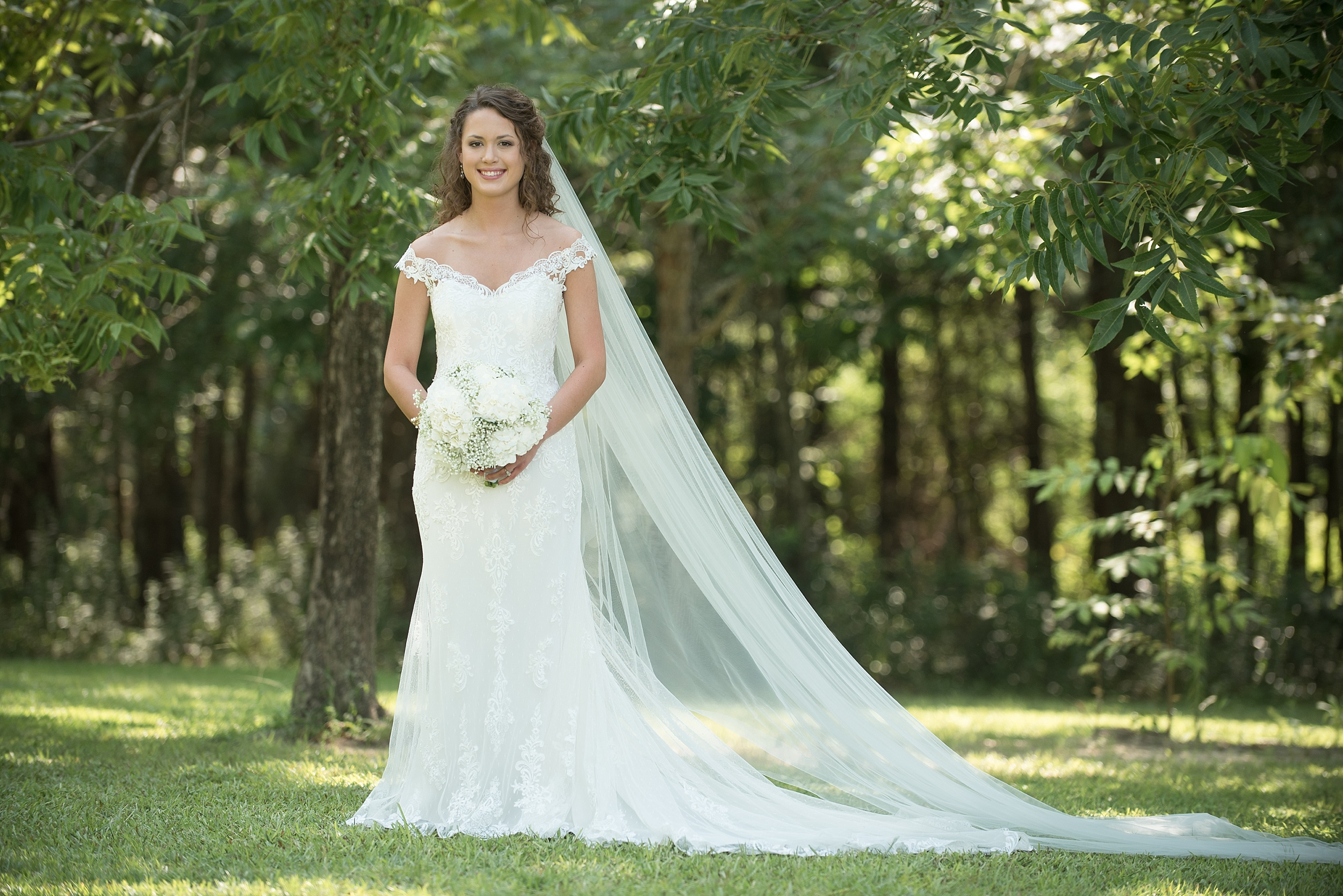 lovely bride in lace wedding dress with cathedral length veil standing underneath lush green trees on a sunny summer day