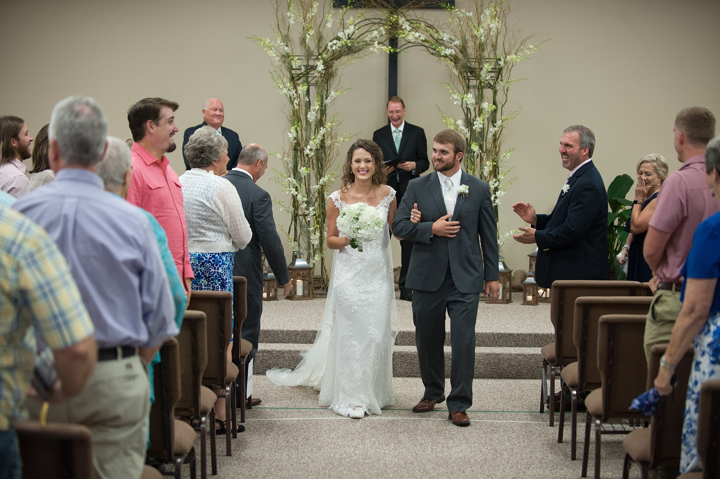 the happy married couple come down the isle as teary parents and friends clap and cheer