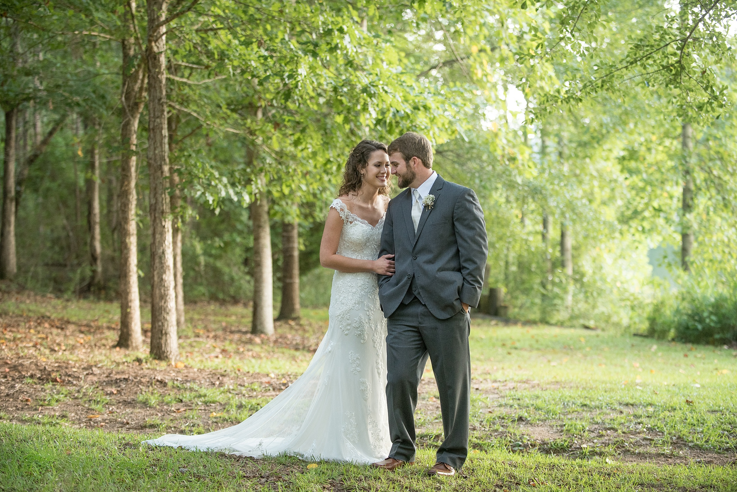 Bride and groom shown full length in the wooded area at Hickory Ridge Lodge in Andalusia, Alabama