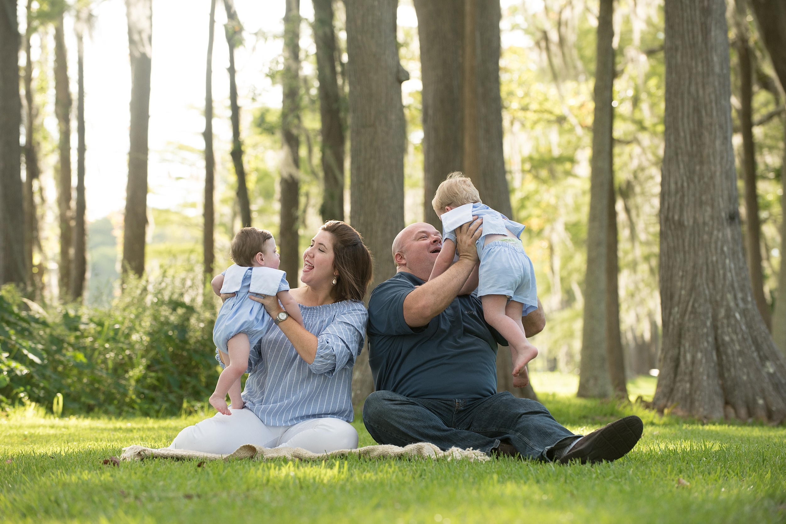 mom and dad playfully hold their sons up in the air while sitting under majestic cypress trees