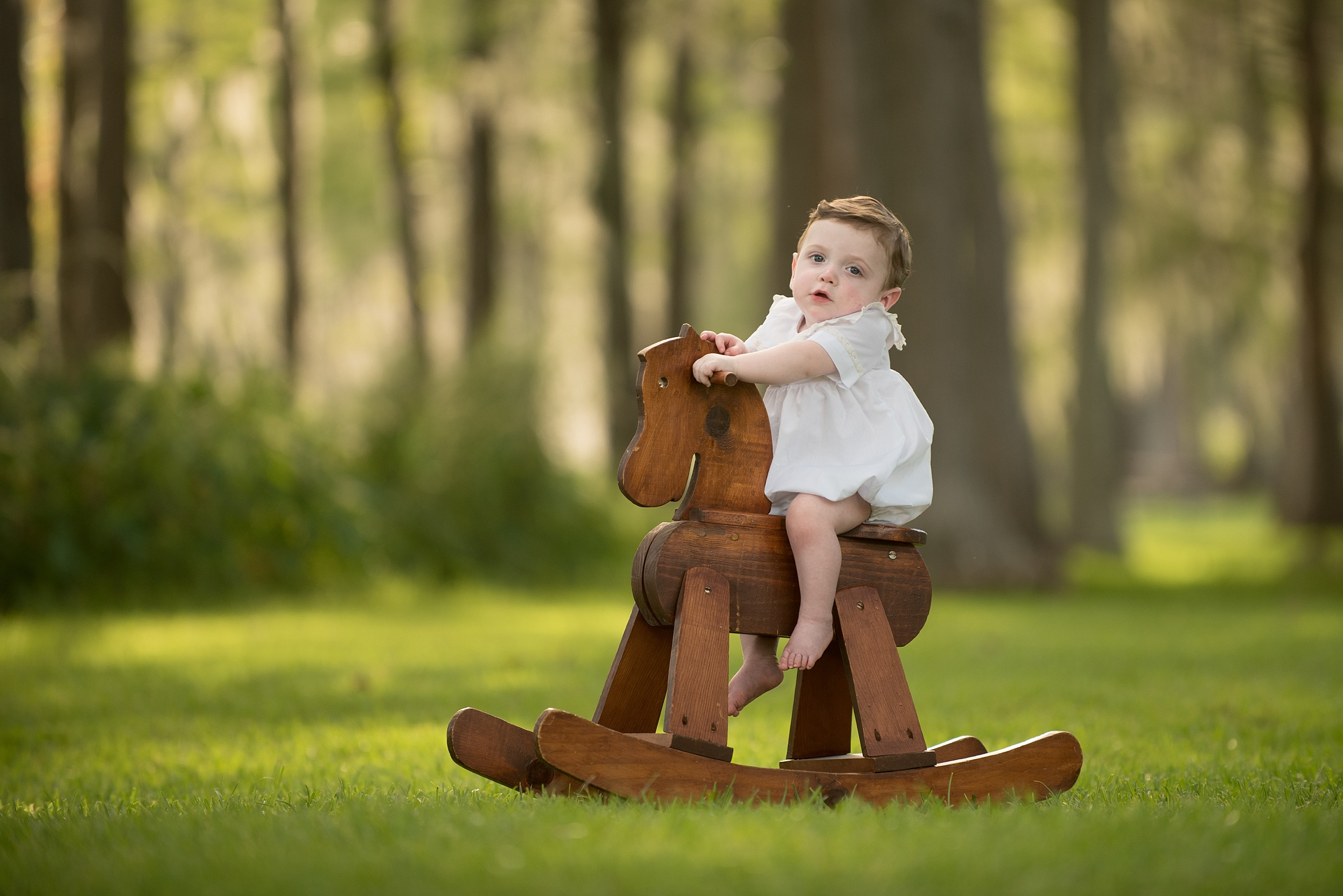 one year old infant boy in white heirloom outfit sits on an antique rocking horse outdoors