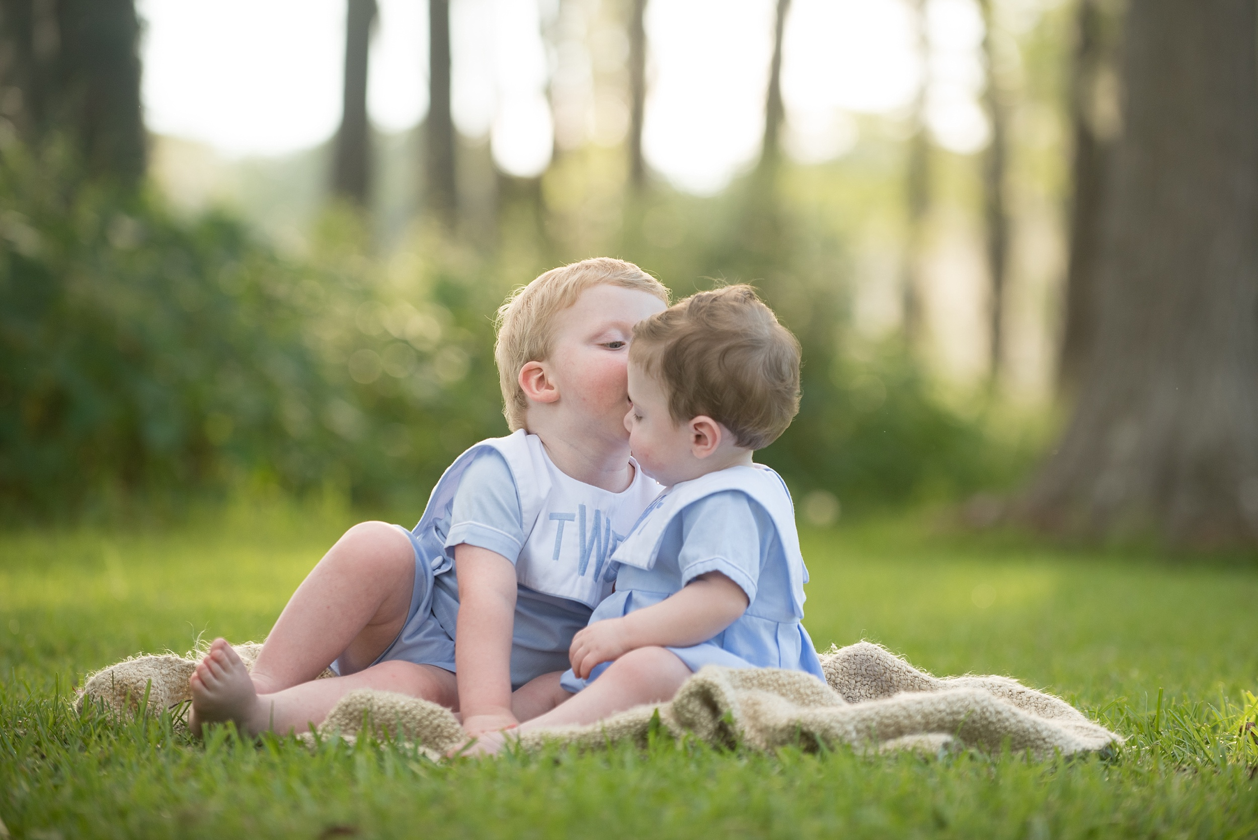 big brother kisses little brother in front of cypress trees