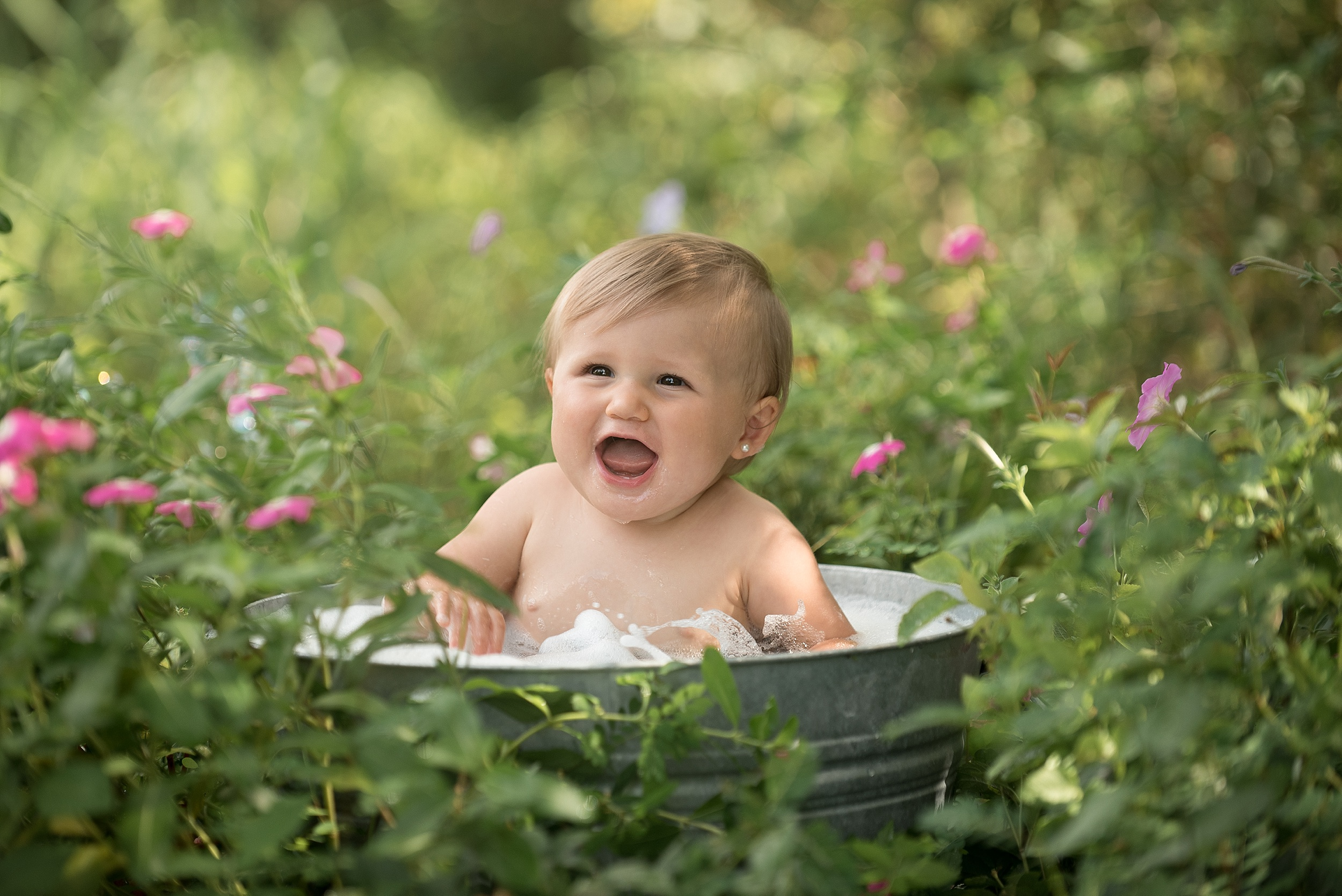one year old girl splashes in a bubble bath outdoors