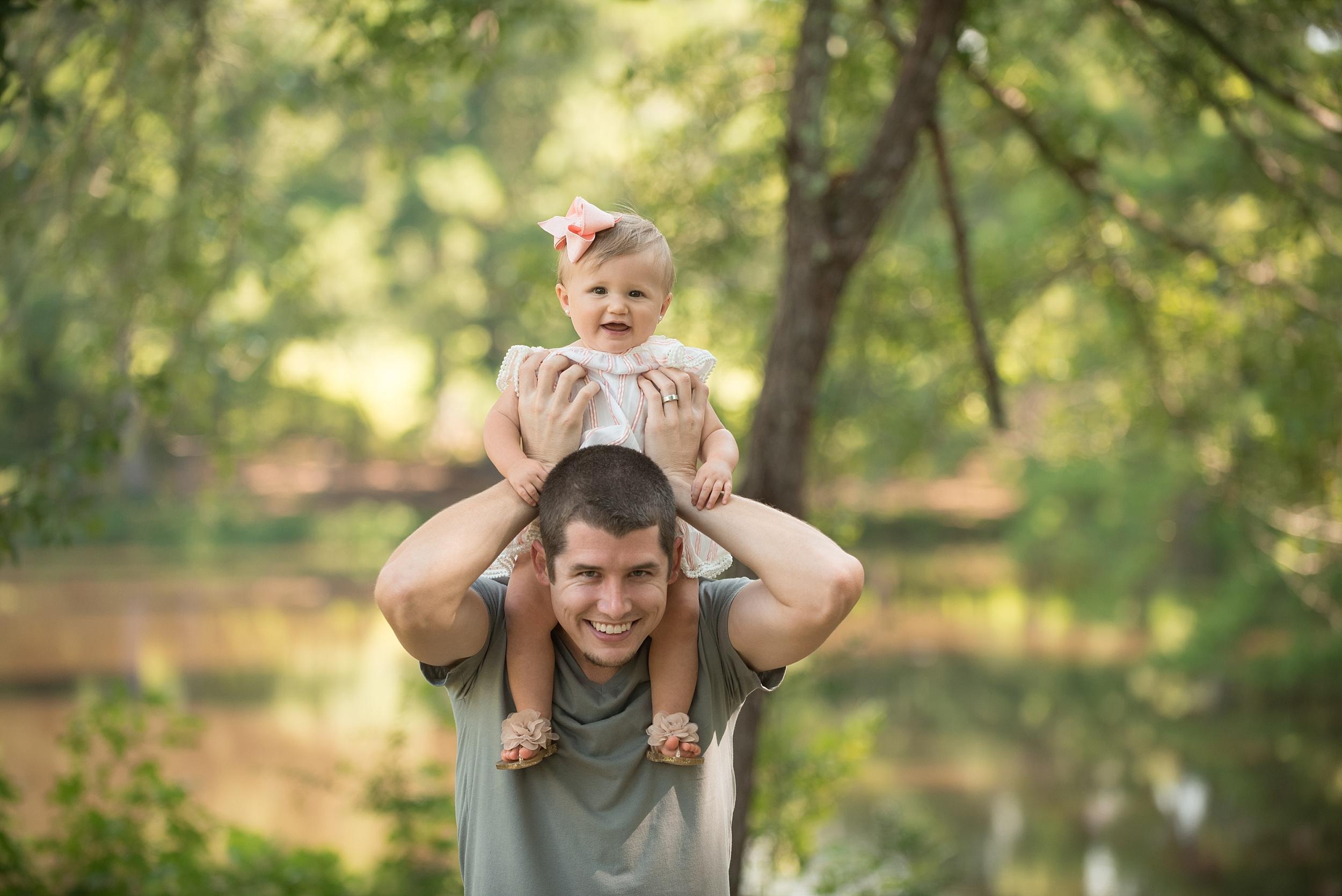 toddler girl rides on her dad's shoulders