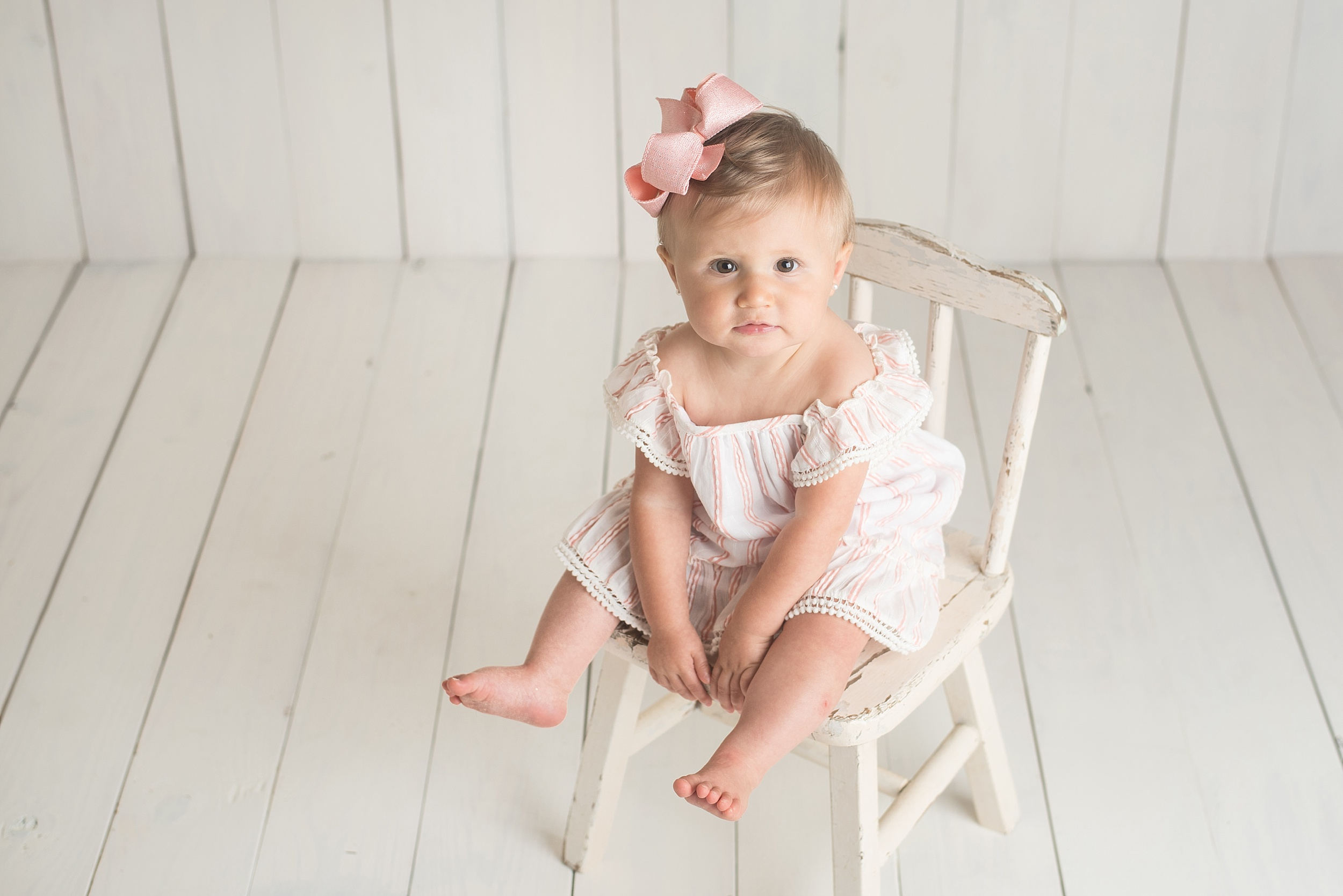 toddler girl with pink dress sits in an old white chair on a white wooden backdrop