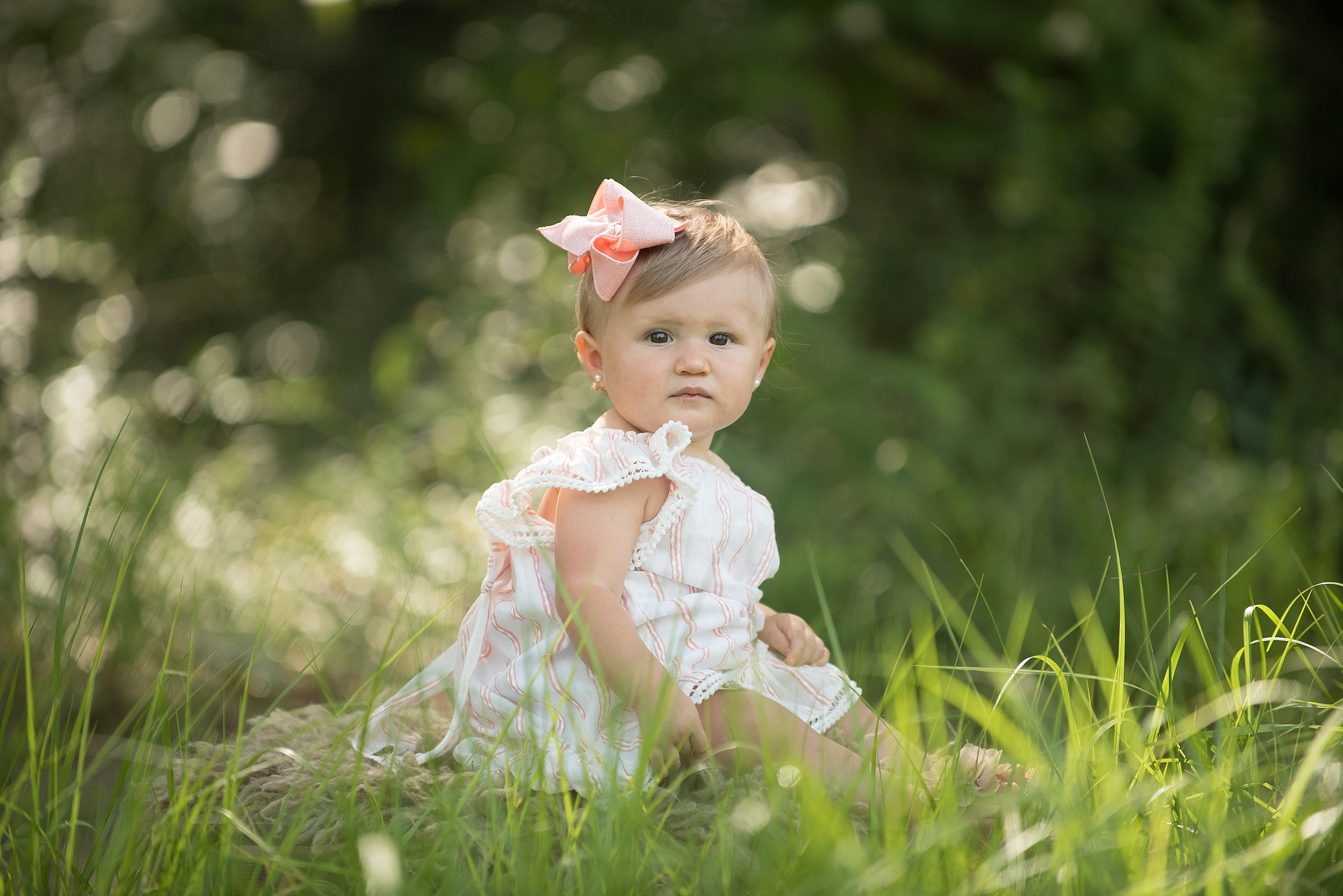 one year old girl with pink bow in a beautiful green outdoor setting
