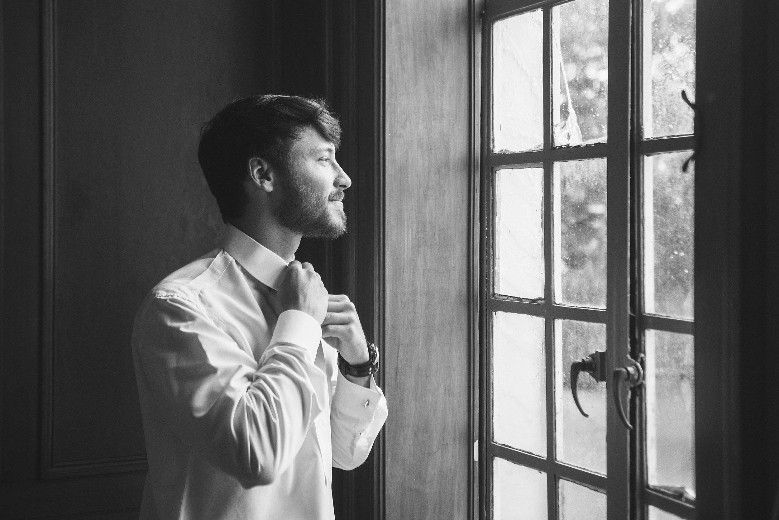 Groom fixes his tie in front of a window