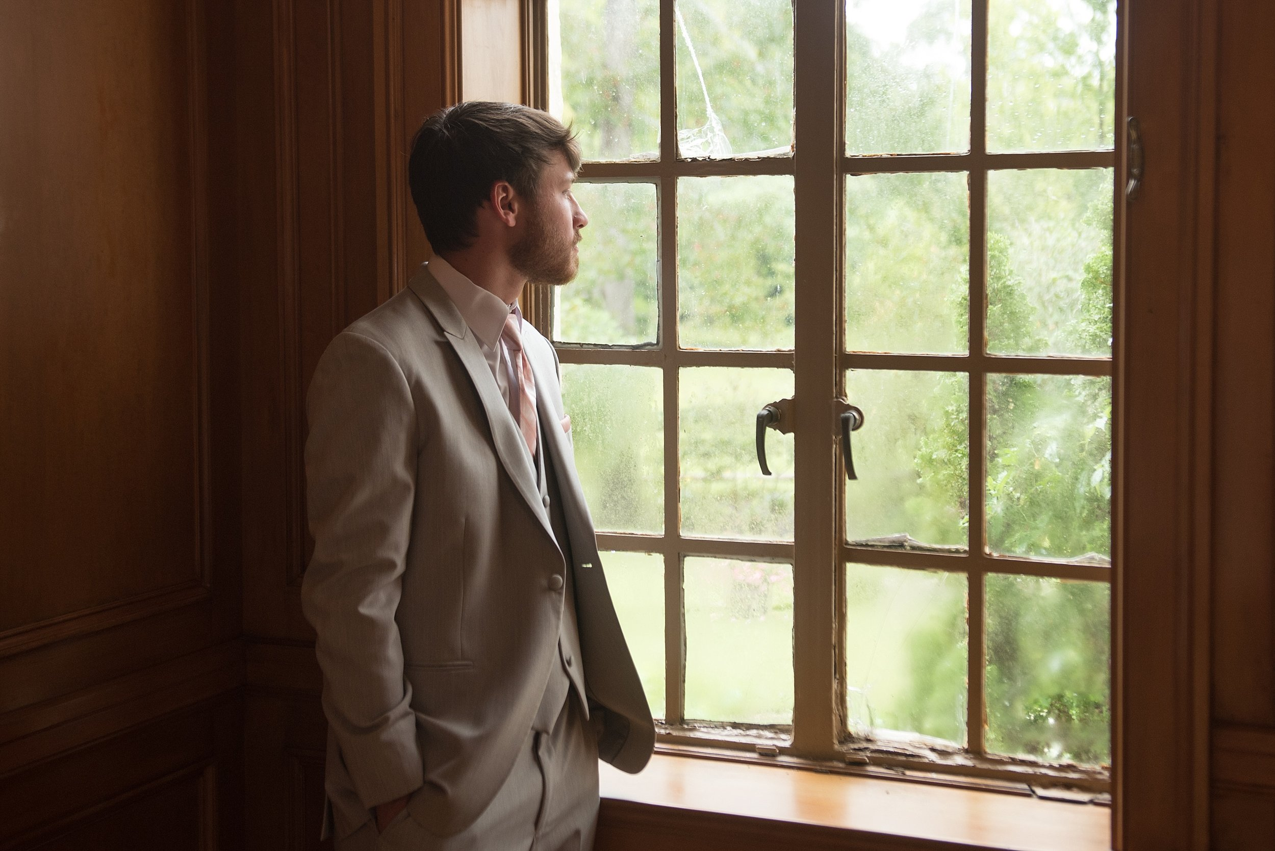 Groom in gray tuxedo looks out of a window before his wedding