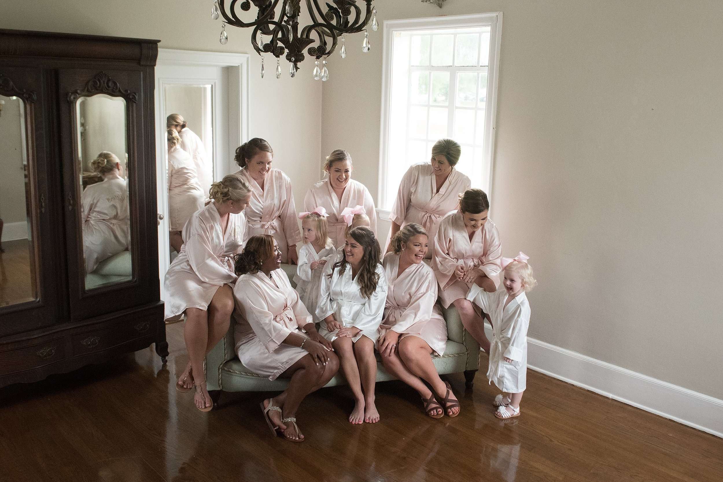 bride and bridesmaids in silk robes laugh together