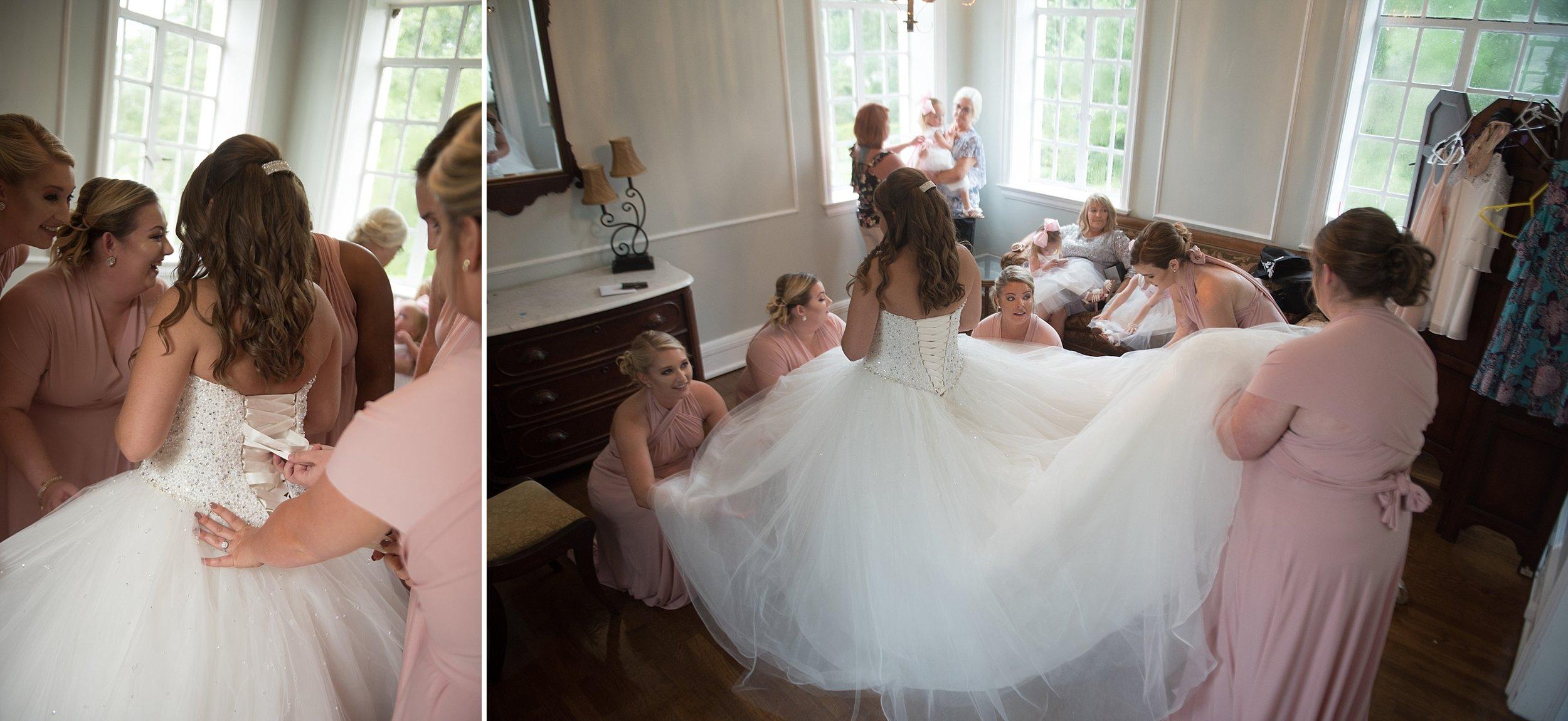 Bridesmaids help bride lace up her ballgown wedding dress