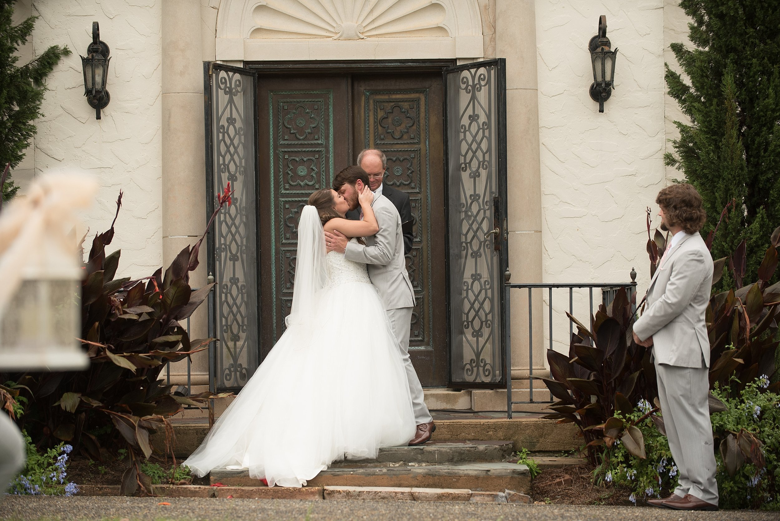Bride and groom have their first kiss as husband and wife during their wedding ceremony at Springdale in Andalusia, Alabama