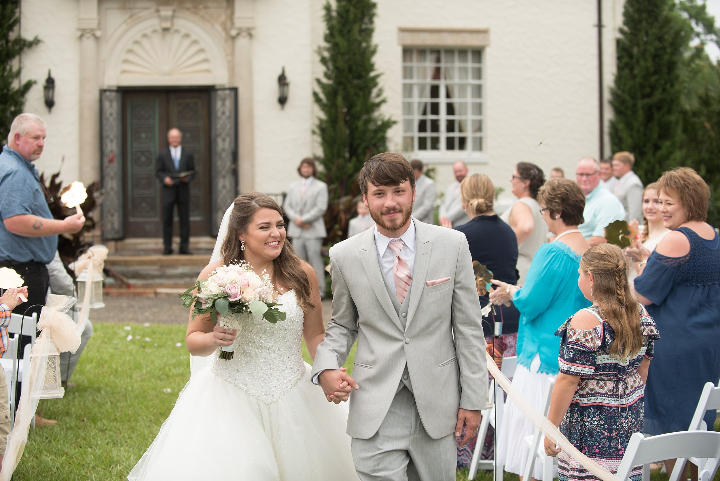 The newly married couple smiles at their guests as they walk down the aisle