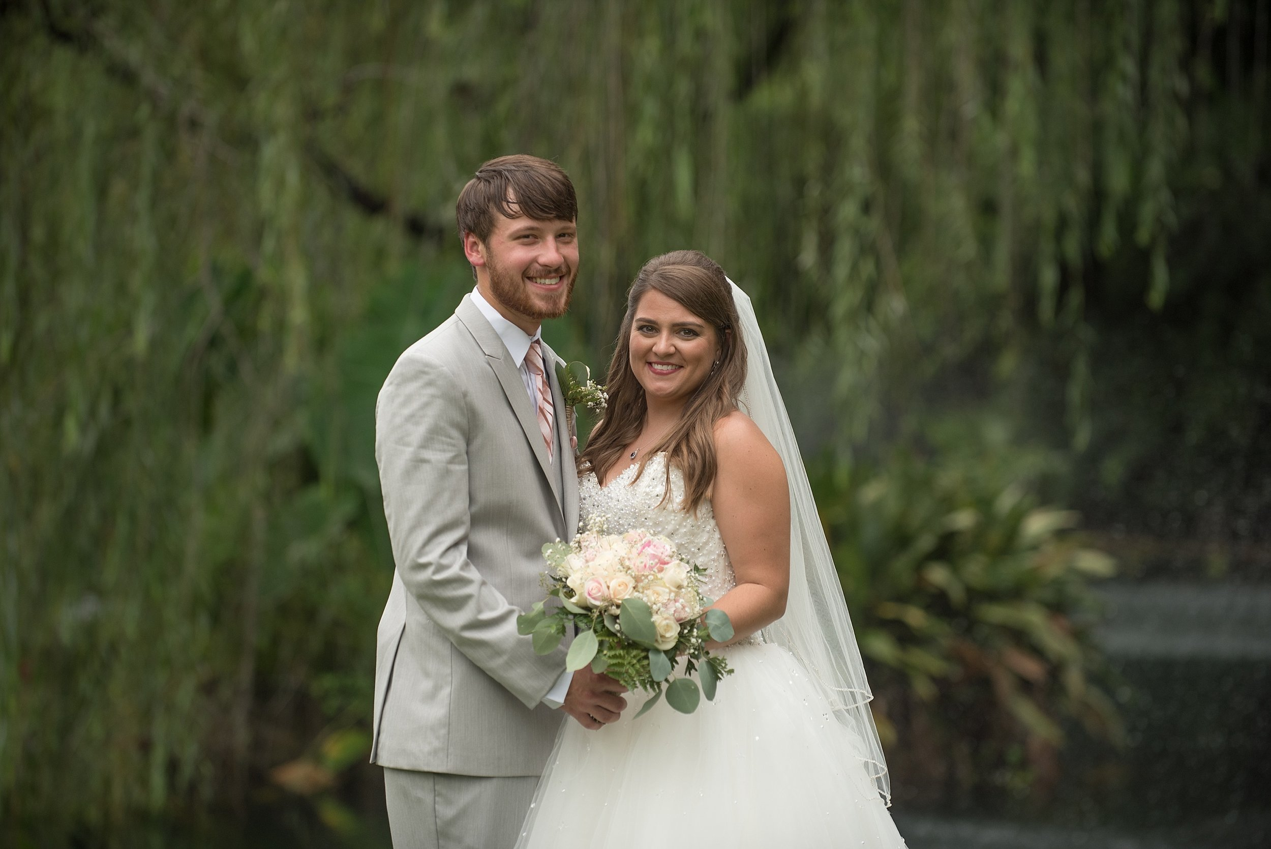 Brides in white sequin ballgown and groom in gray tuxedo hold a beautiful bouquet of eucalyptus and pink roses