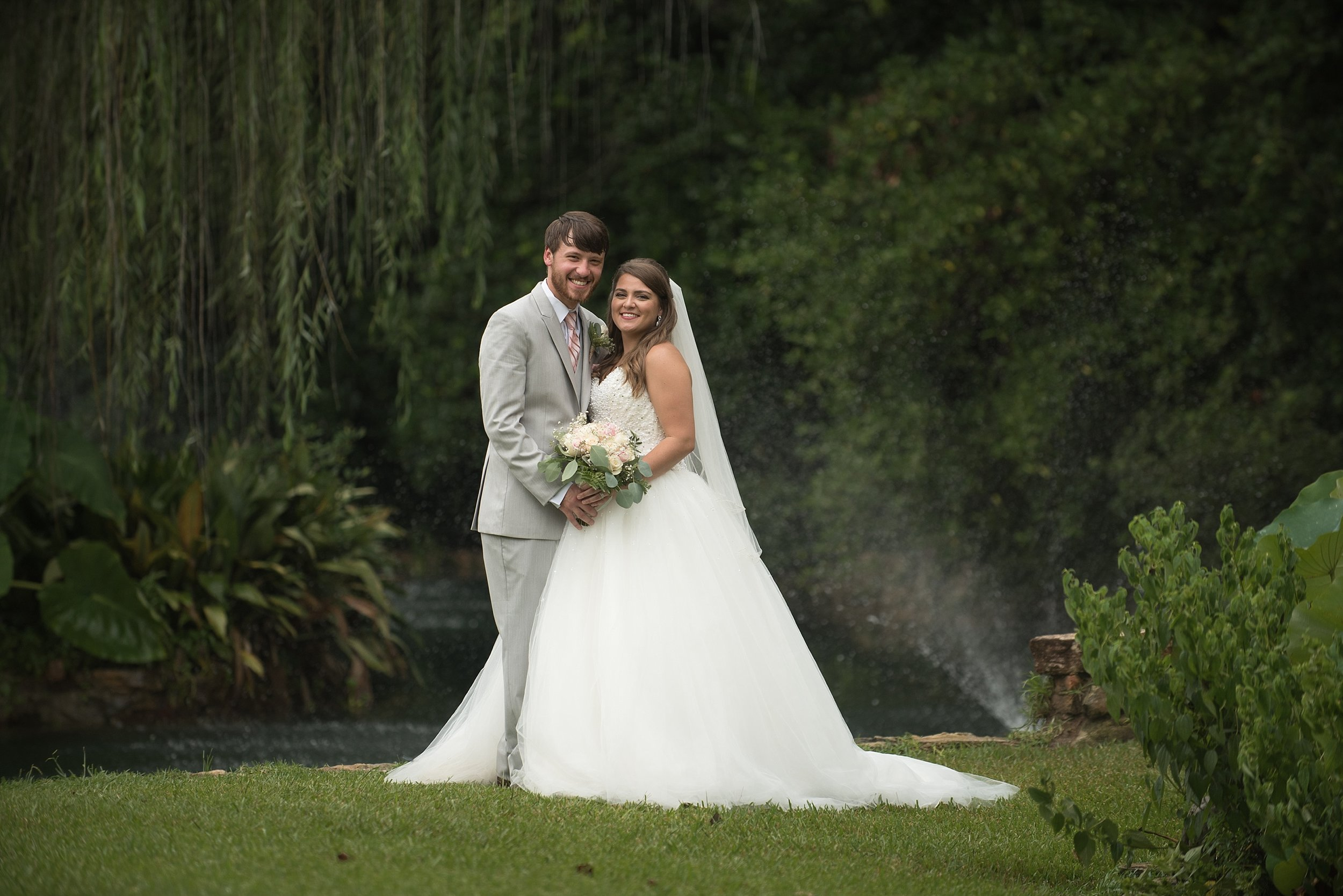 Newlyweds in front of weeping willow tree happily smile