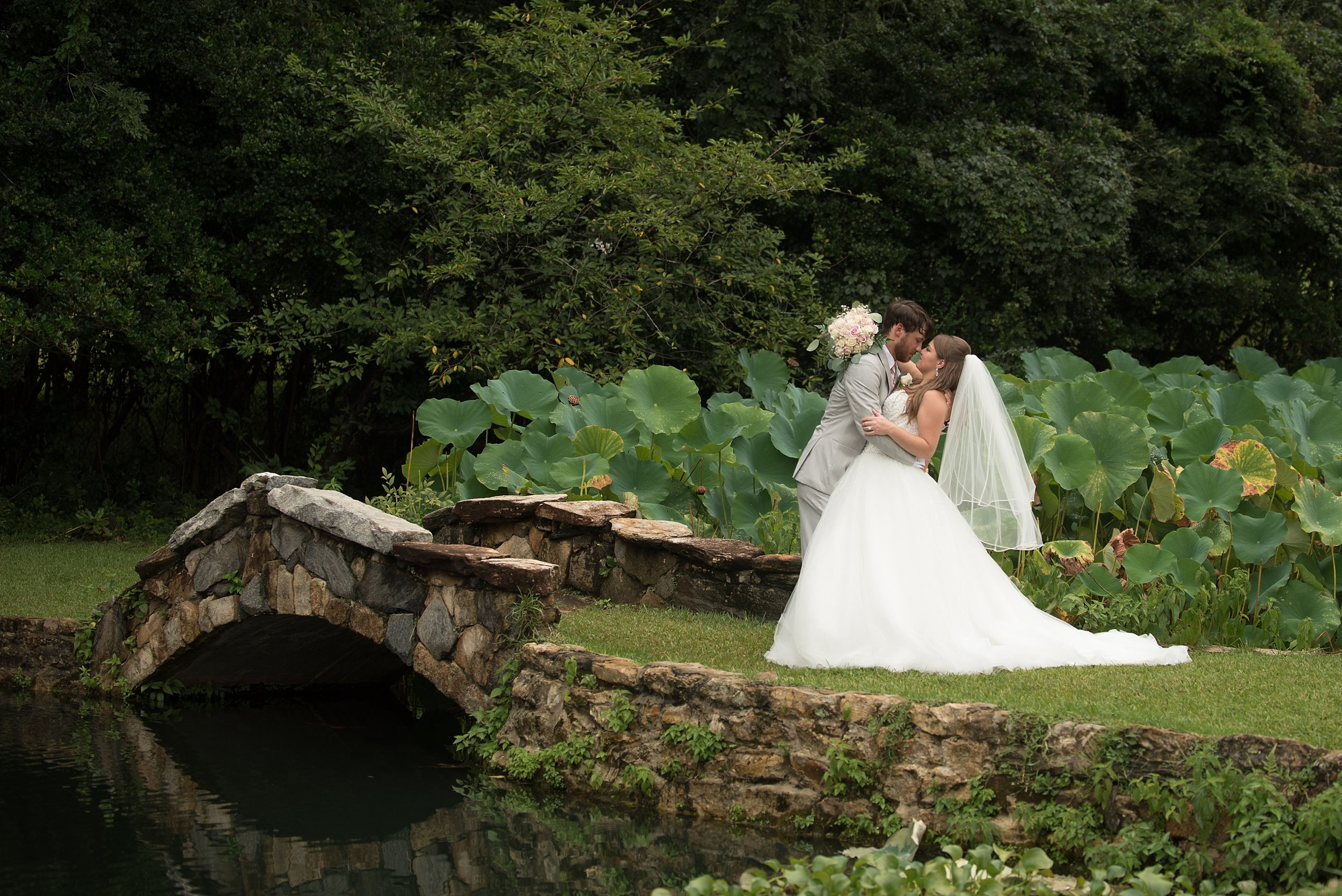 Groom dips bride and gives her a kiss beside a stone bridge