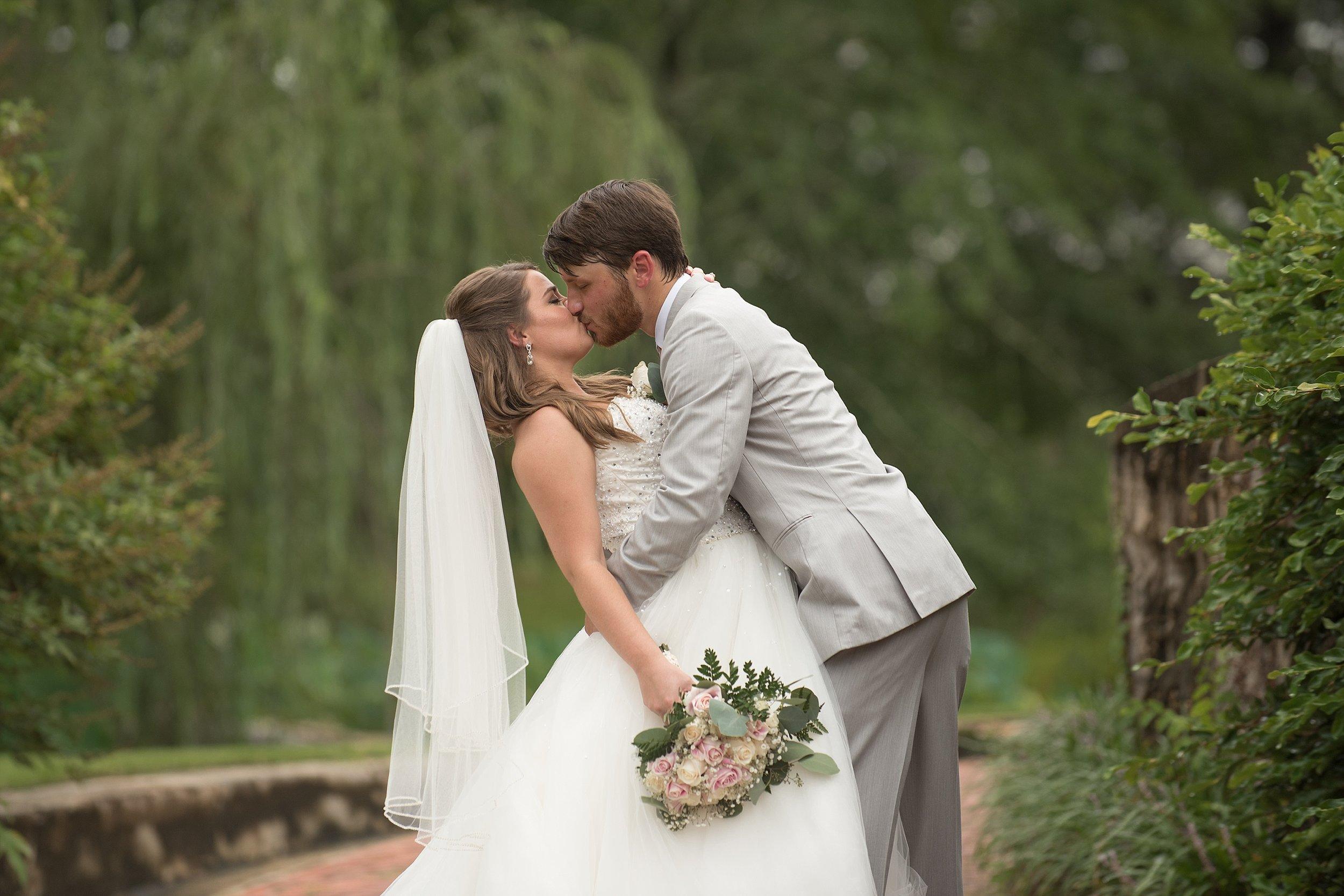 Groom kisses his beautiful bride in a white ballgown wedding dress