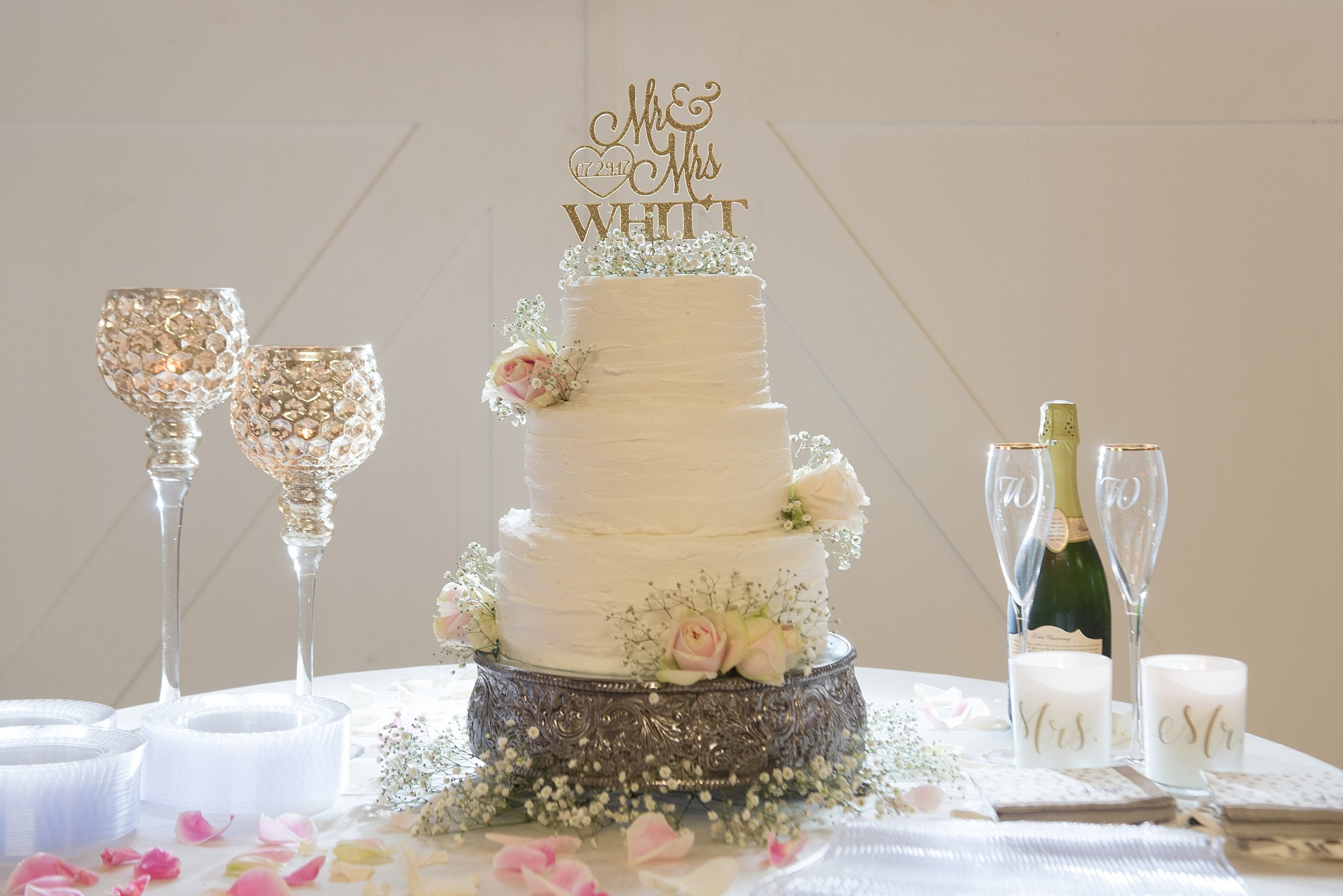 three tier white wedding cake with pink rose accents