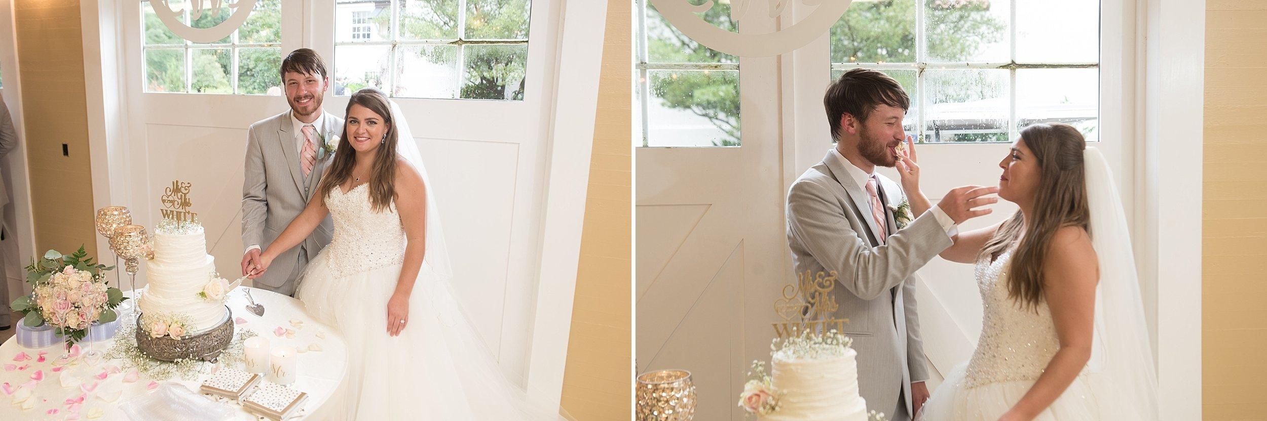 newlyweds cut their three tier white wedding cake