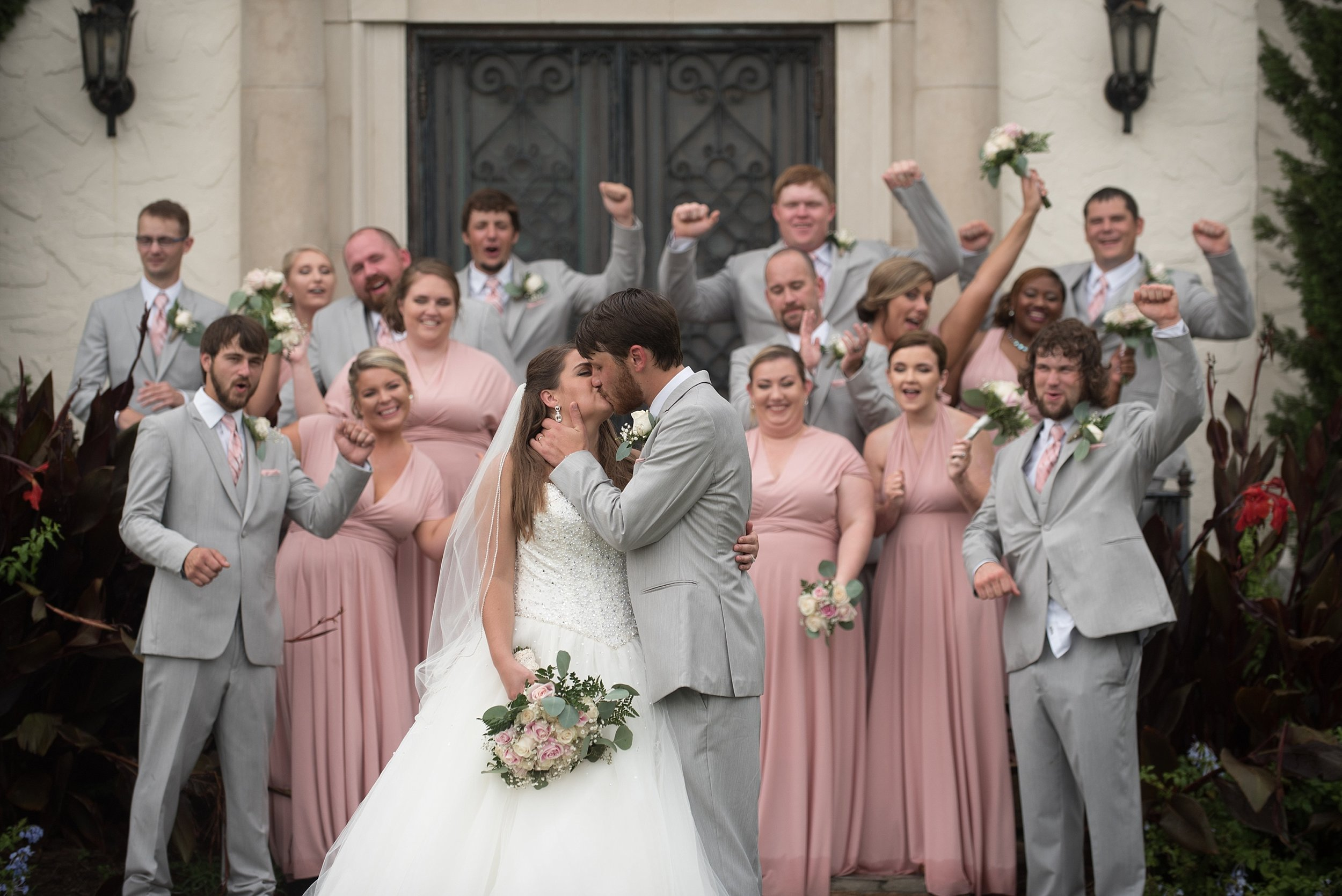 Wedding party cheers behind bride and groom on the steps of Springdale in Andalusia, Alabama