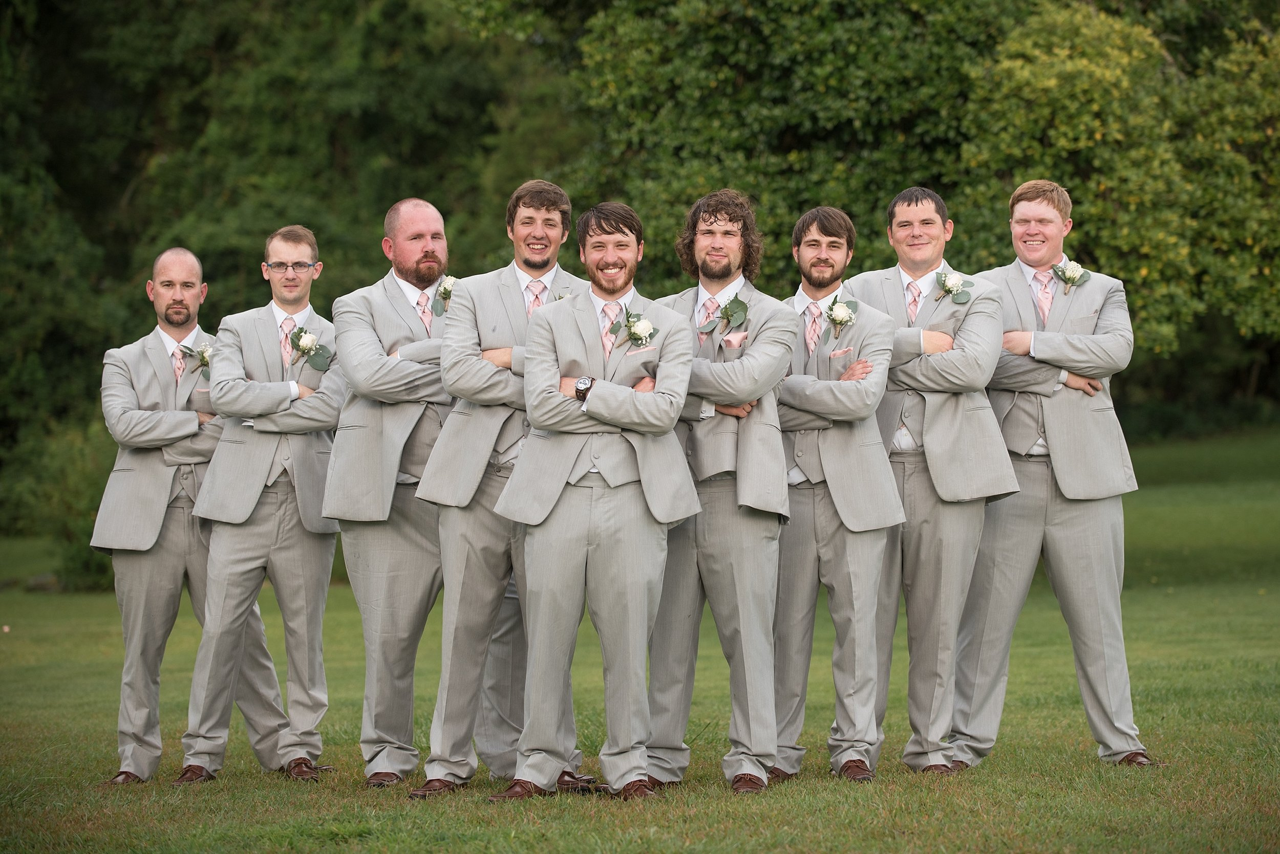 groomsmen in gray tuxedos stand in a V formation with the groom at the point